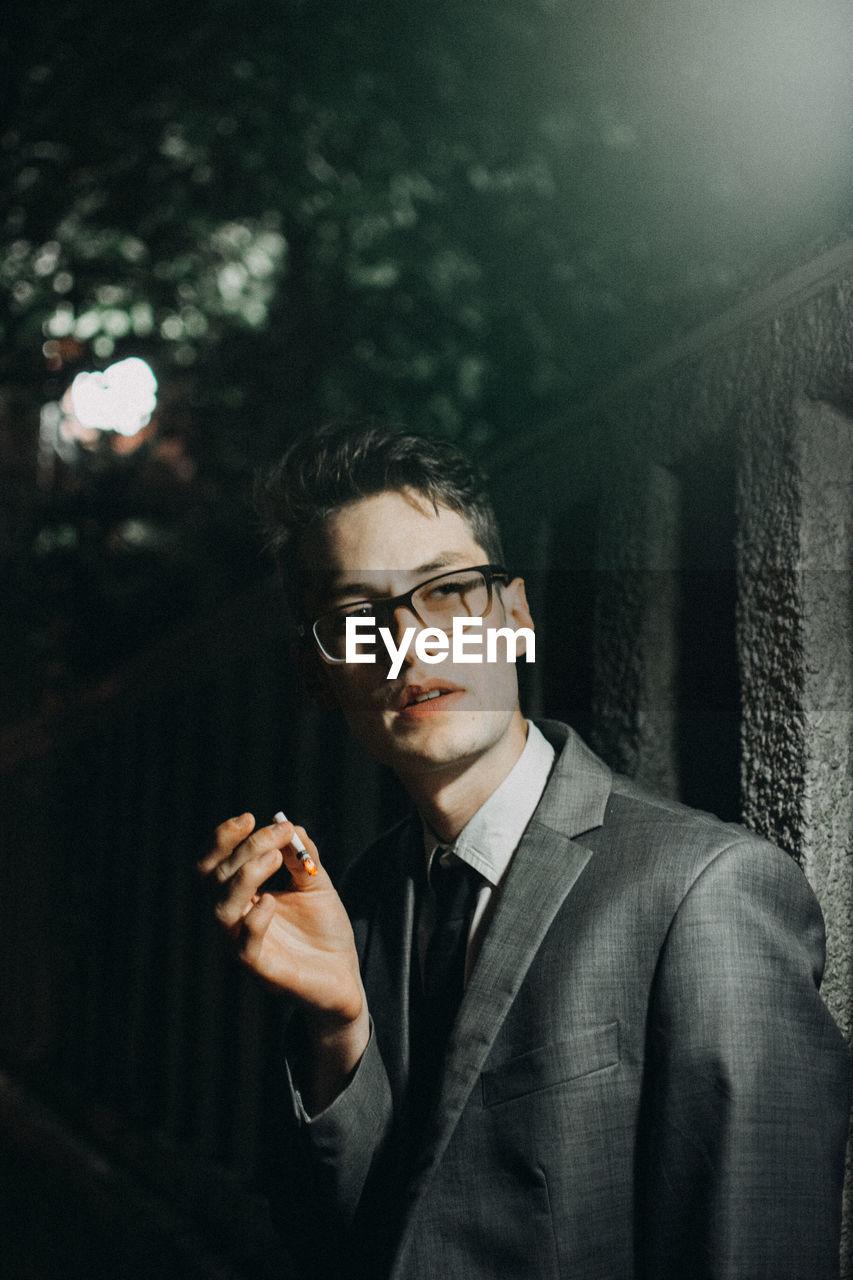 Businessman Smoking Cigarette By Illuminated Wall At Night