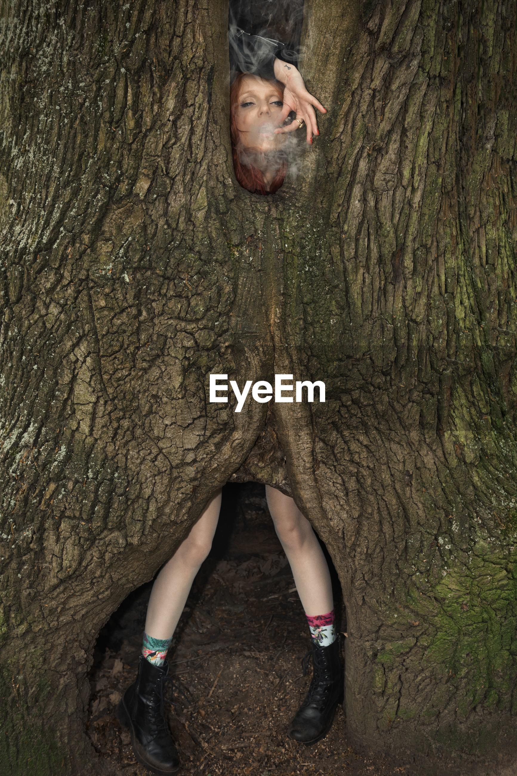 Woman exhaling smoke by tree