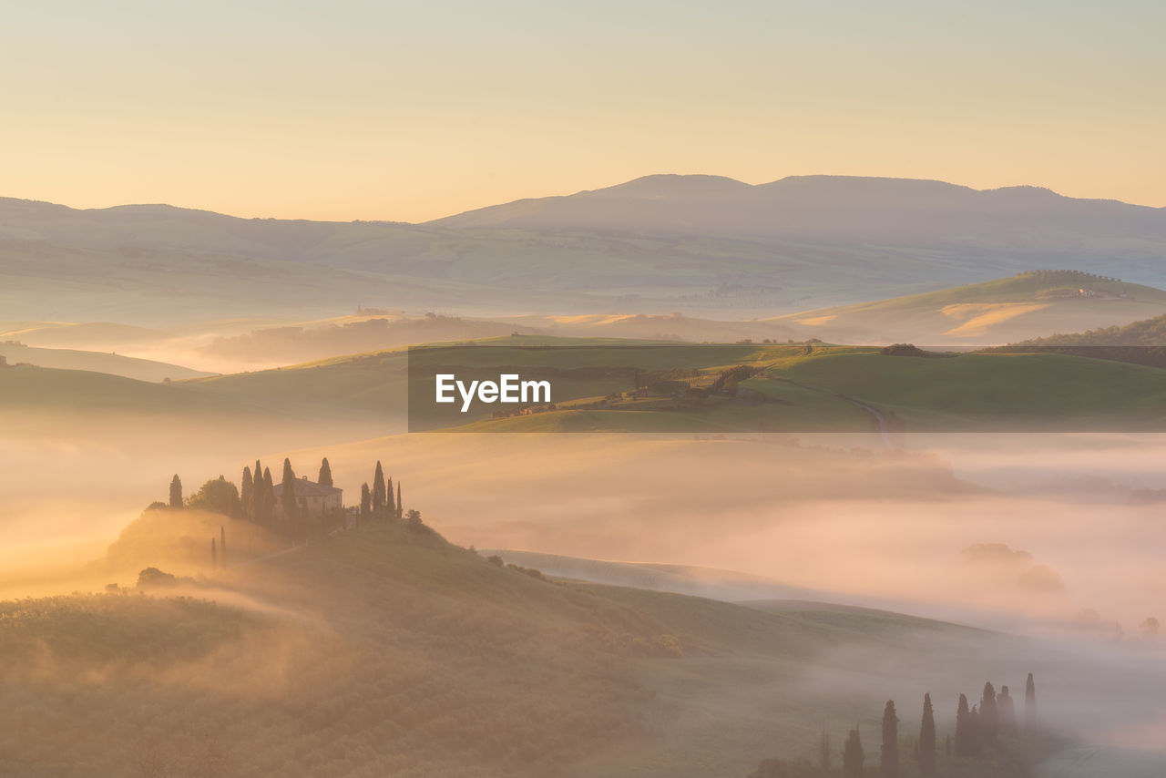 sky, mountain, sunset, scenics - nature, fog, beauty in nature, nature, architecture, orange color, built structure, building exterior, tranquil scene, mountain range, travel destinations, religion, no people, travel, history, the past, tranquility, outdoors, ancient civilization