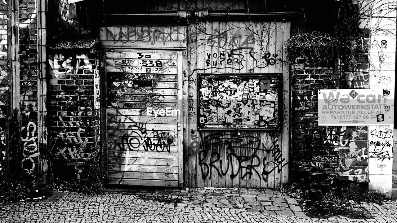 graffiti, architecture, built structure, door, entrance, building exterior, text, no people, day, wall - building feature, western script, communication, building, non-western script, creativity, script, outdoors, abandoned, wall, messy