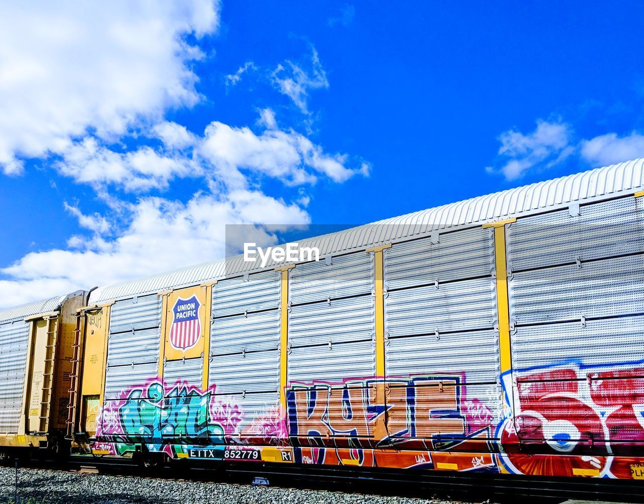 GRAFFITI ON TRAIN AGAINST BLUE SKY AND CLOUDS