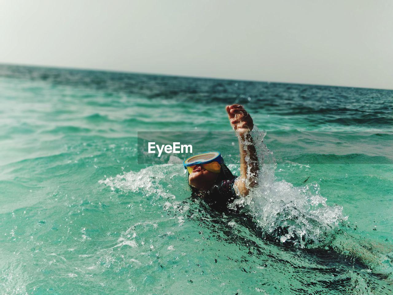 Girl Swimming In Sea Against Sky