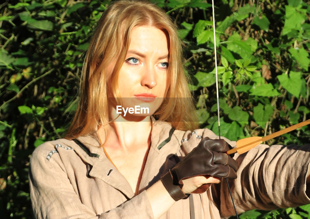 Close-Up Of Confident Young Woman Aiming Bow In Forest During Sunny Day