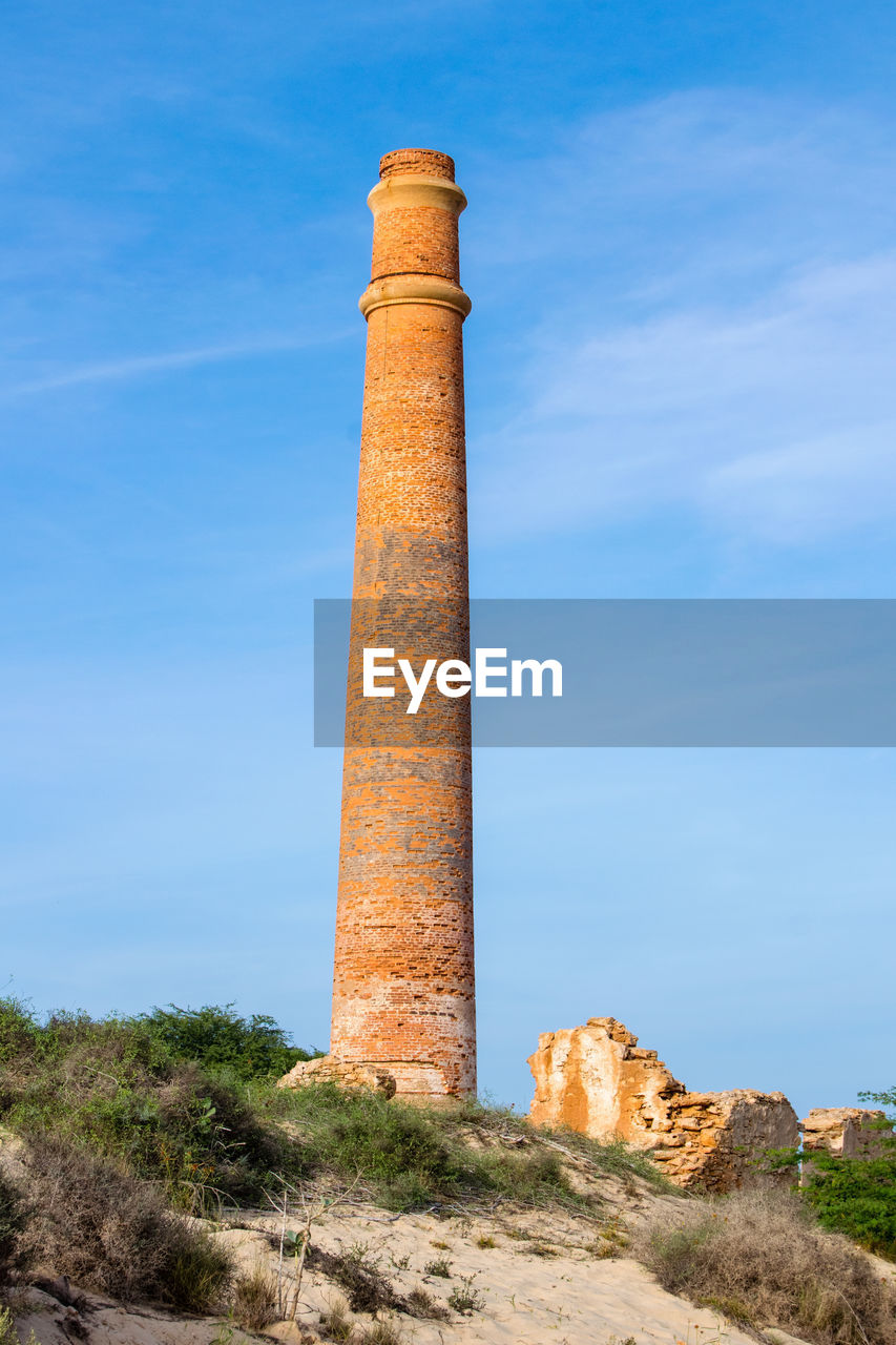 sky, built structure, architecture, nature, blue, day, no people, tall - high, architectural column, low angle view, history, the past, outdoors, travel destinations, plant, building exterior, solid, cloud - sky, travel, sunlight, ruined, ancient civilization