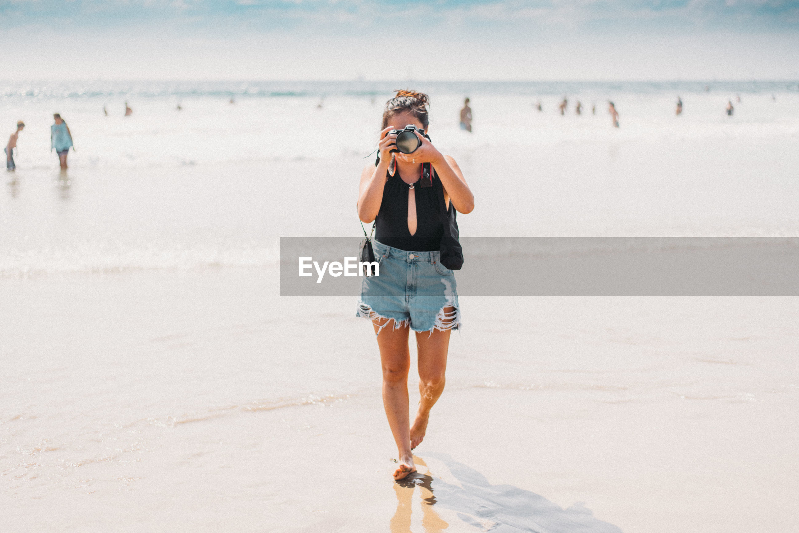 YOUNG WOMAN STANDING ON BEACH
