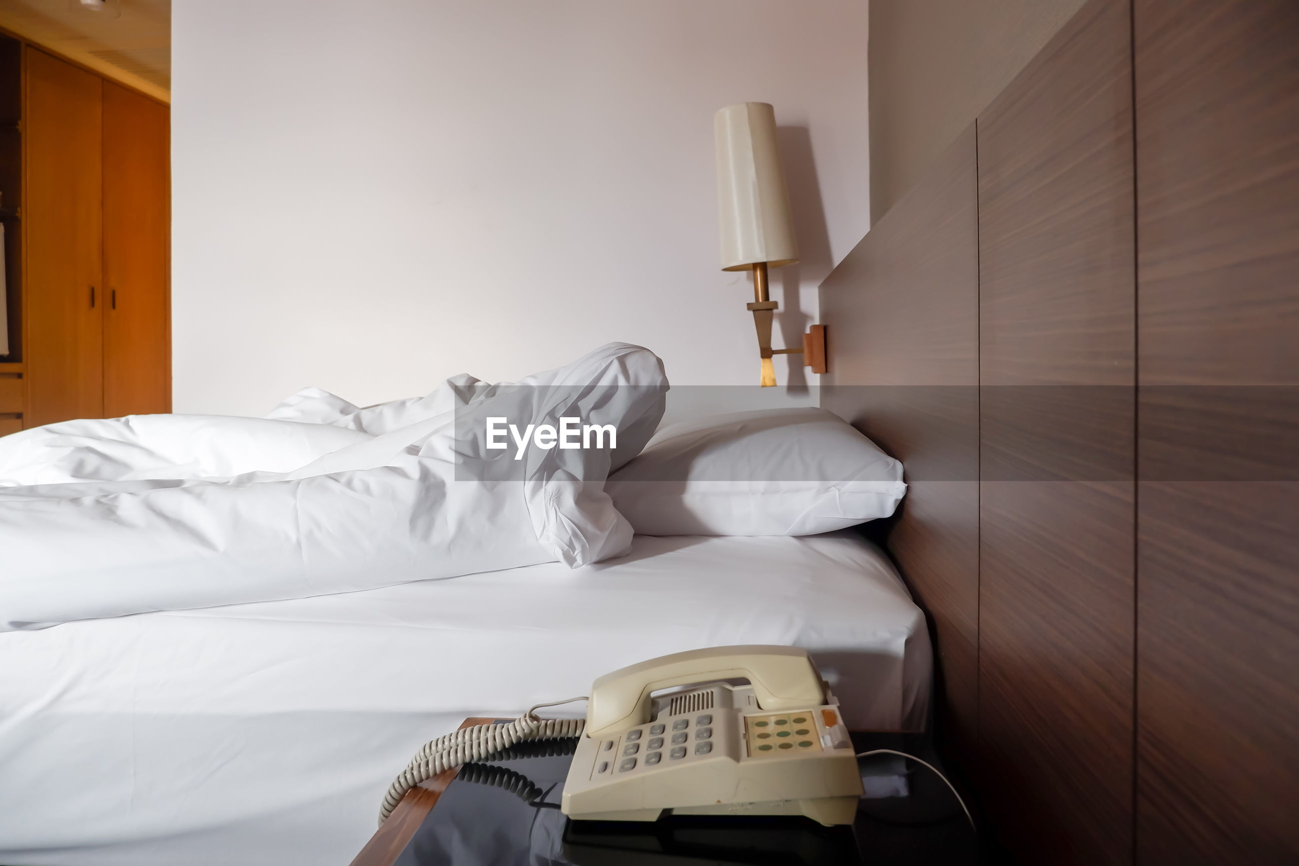 ELECTRIC LAMP ON BED AGAINST HOUSE