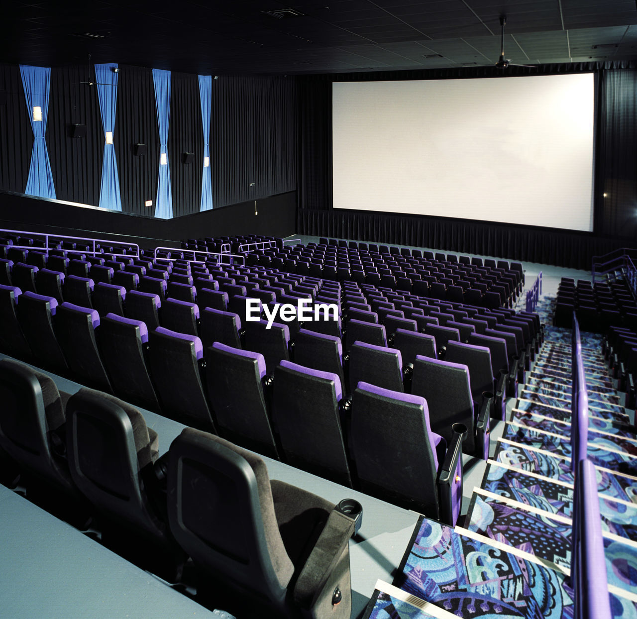 seat, indoors, in a row, auditorium, chair, empty, large group of objects, no people, film industry, architecture, day