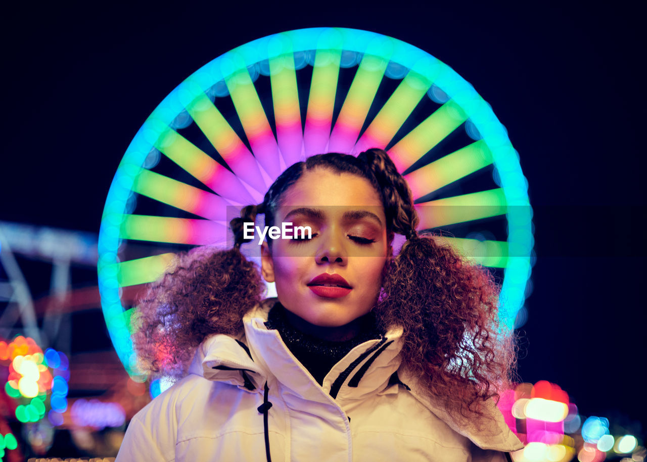 Smiling woman standing against illuminated ferris wheel at night