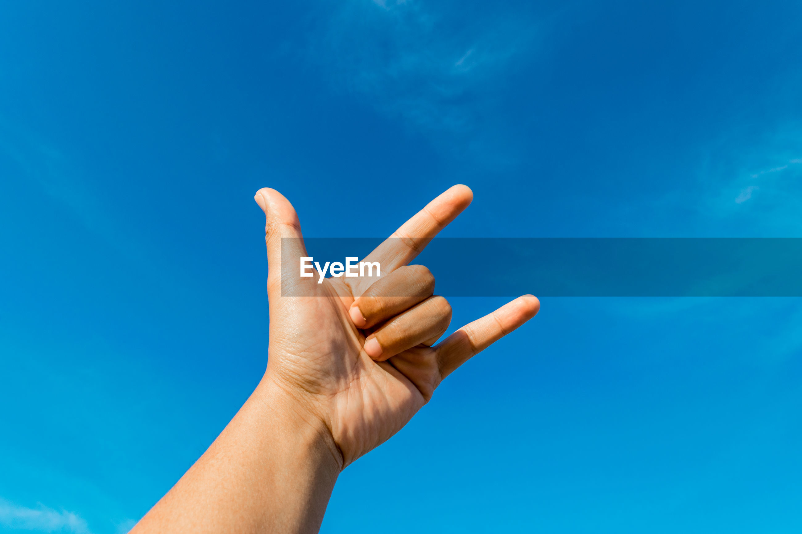 Cropped hand gesturing horn sign against blue sky