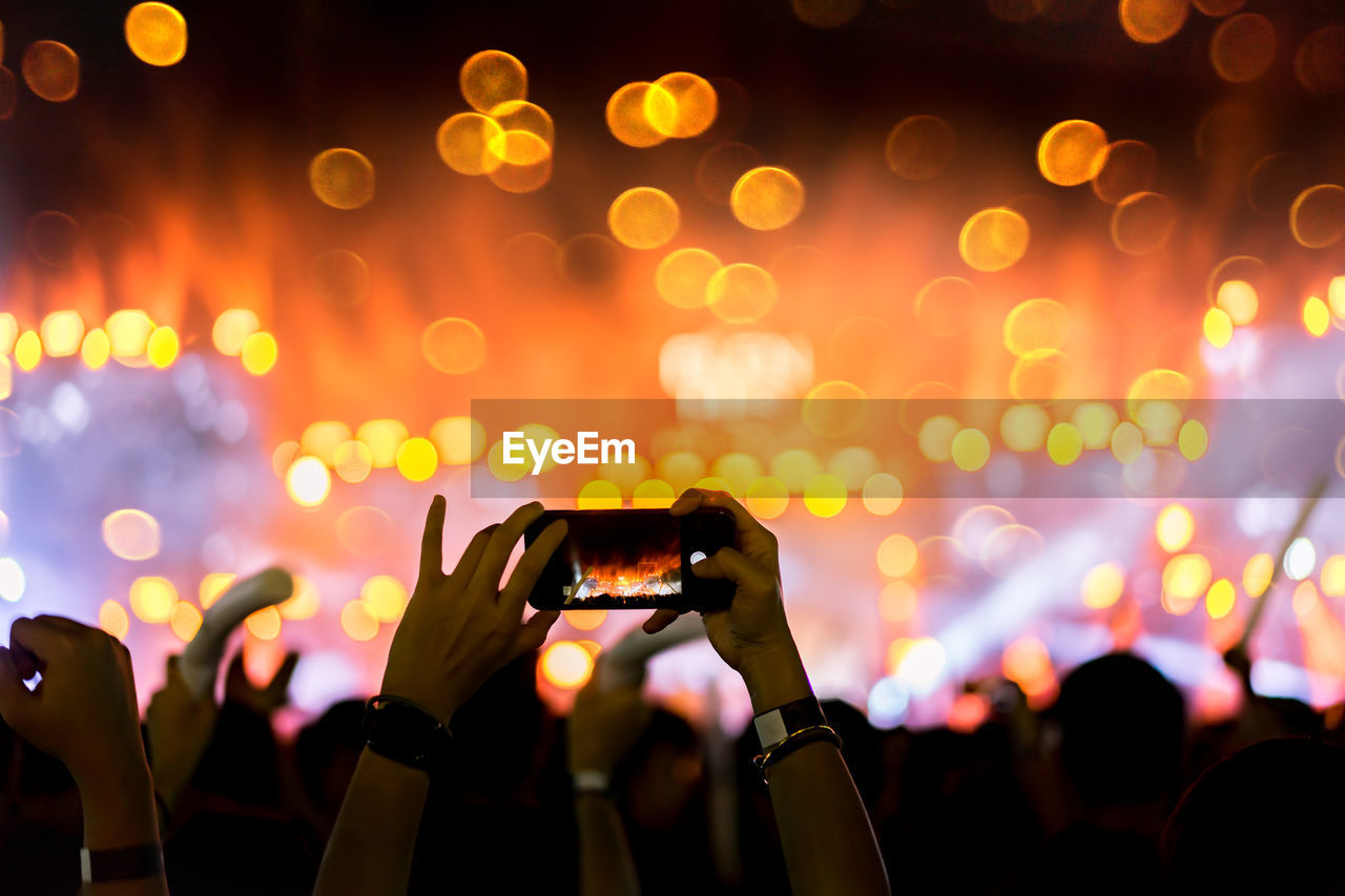 Cropped hands of person photographing with smart phone at music concert