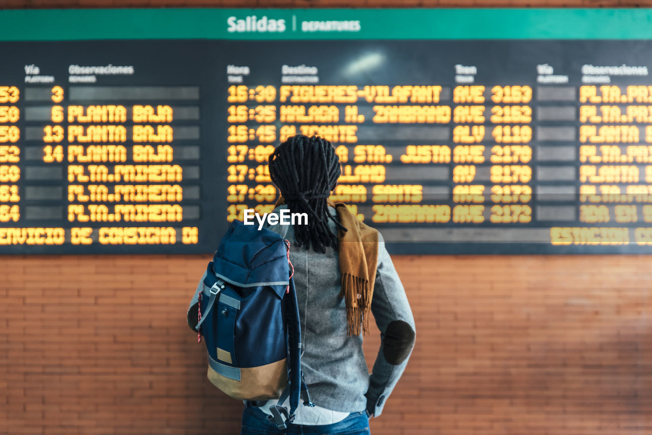 Rear View Of Man Reading Airport Departure Board