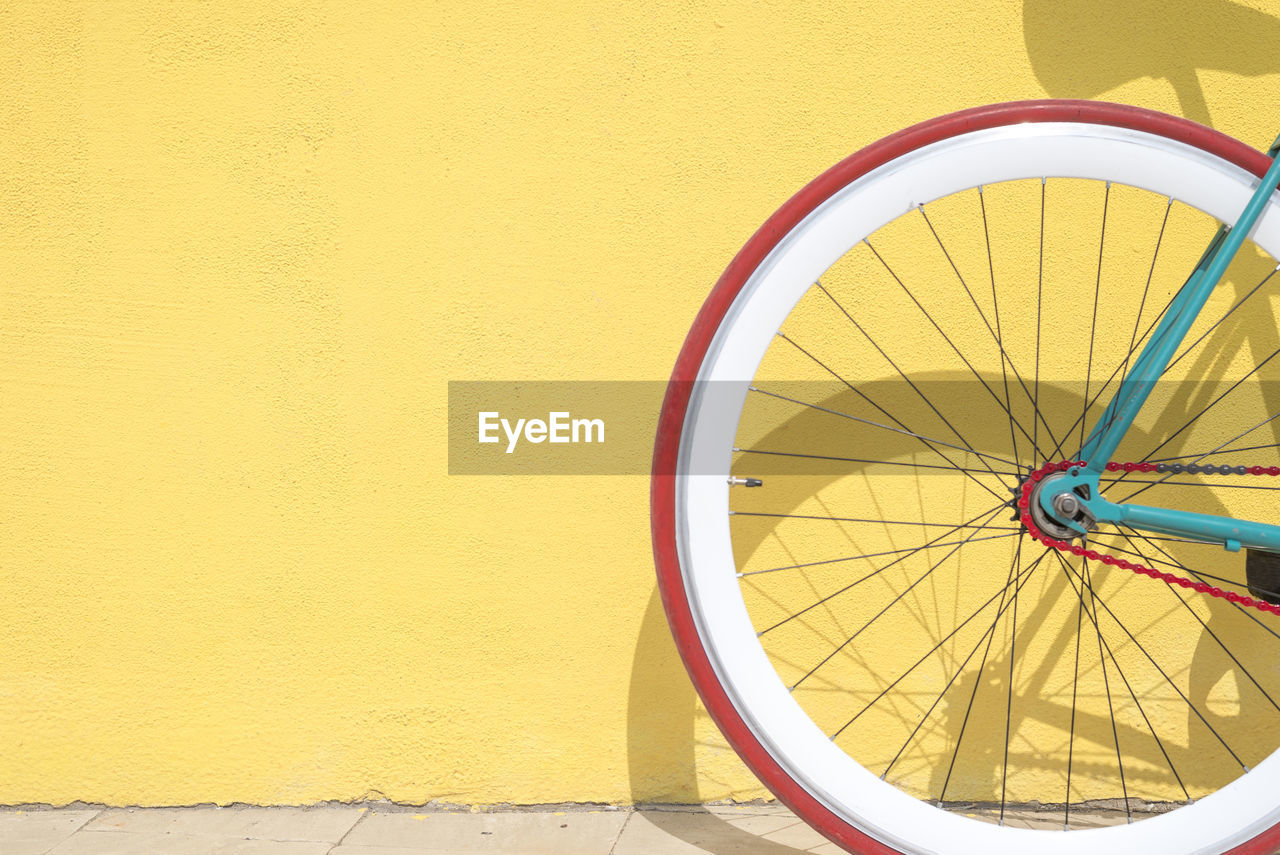 yellow, wheel, transportation, bicycle, mode of transportation, no people, wall - building feature, day, tire, land vehicle, architecture, outdoors, built structure, spoke, stationary, close-up, wall, shape, building exterior, sunlight