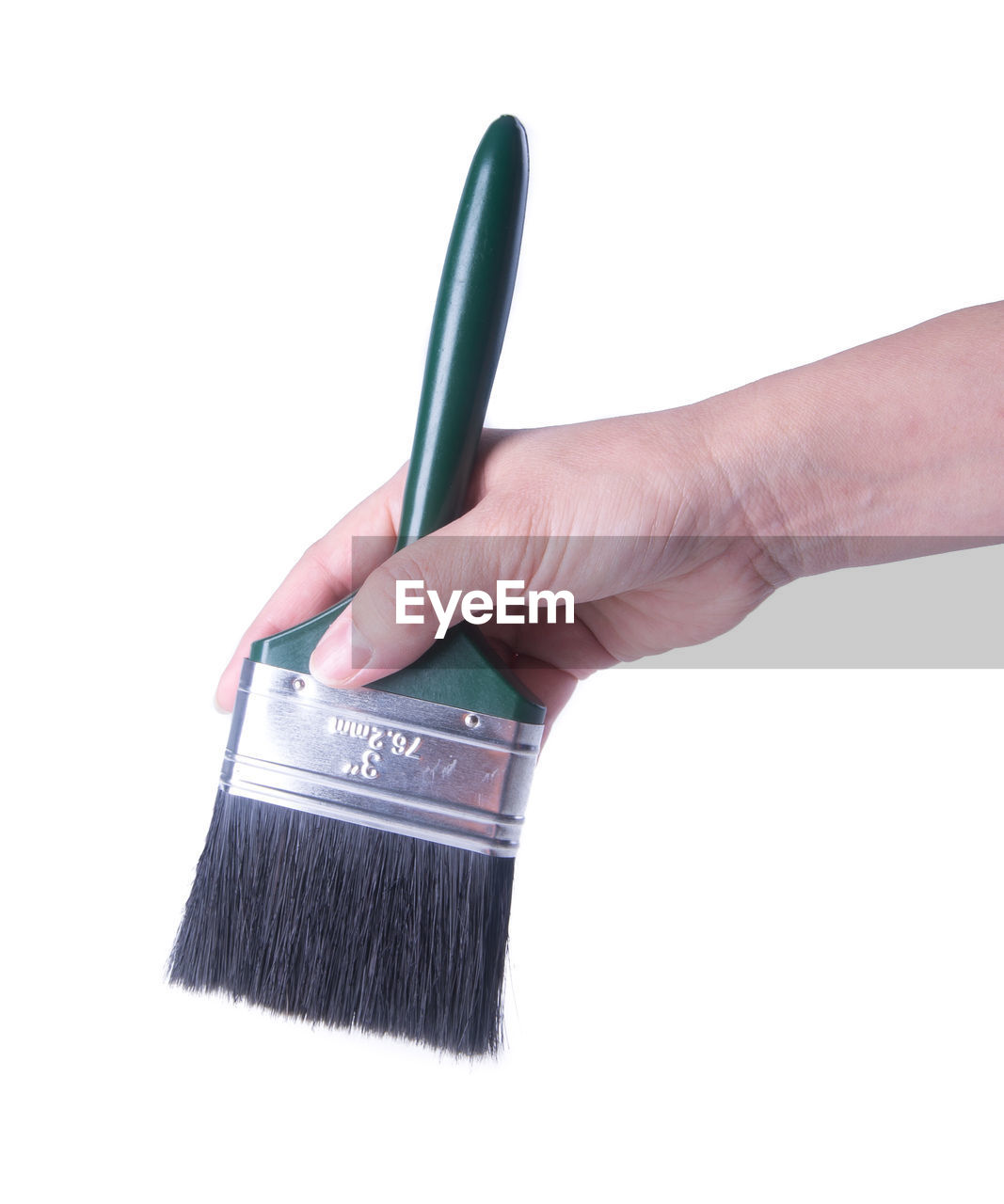 Cropped hand of woman holding paintbrush against white background