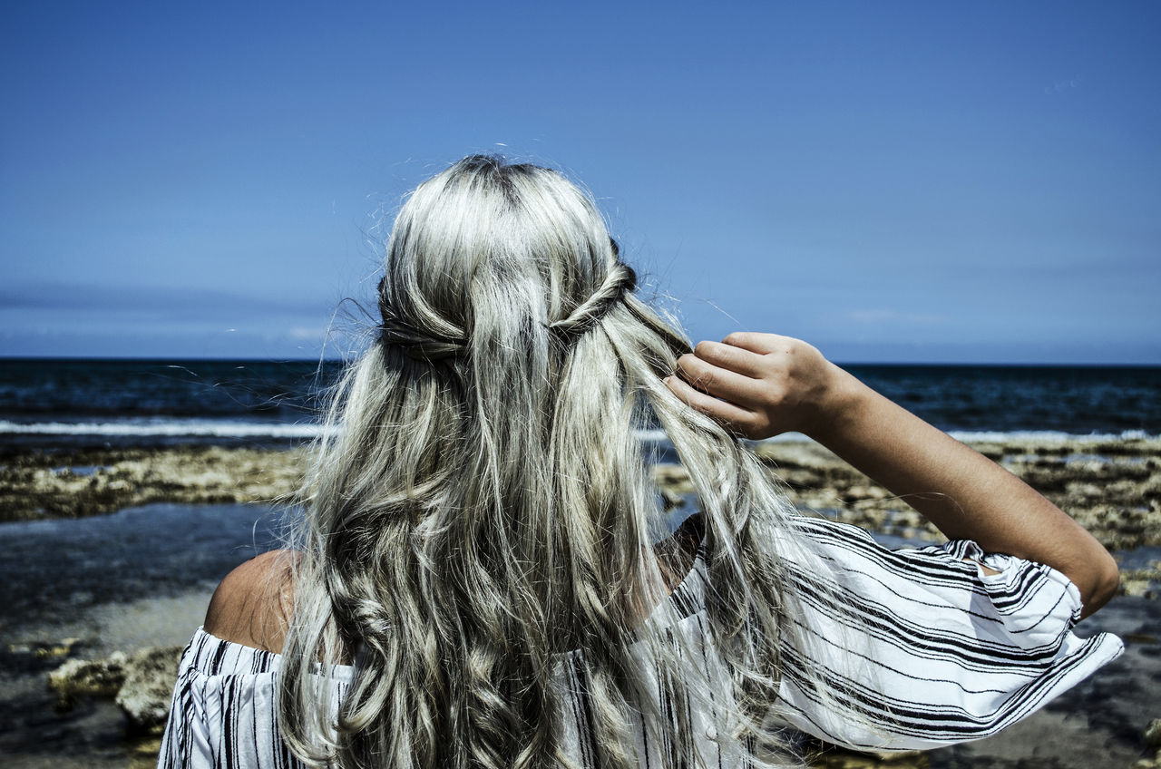 Rear View Of Young Woman Standing At Beach Against Blue Sky