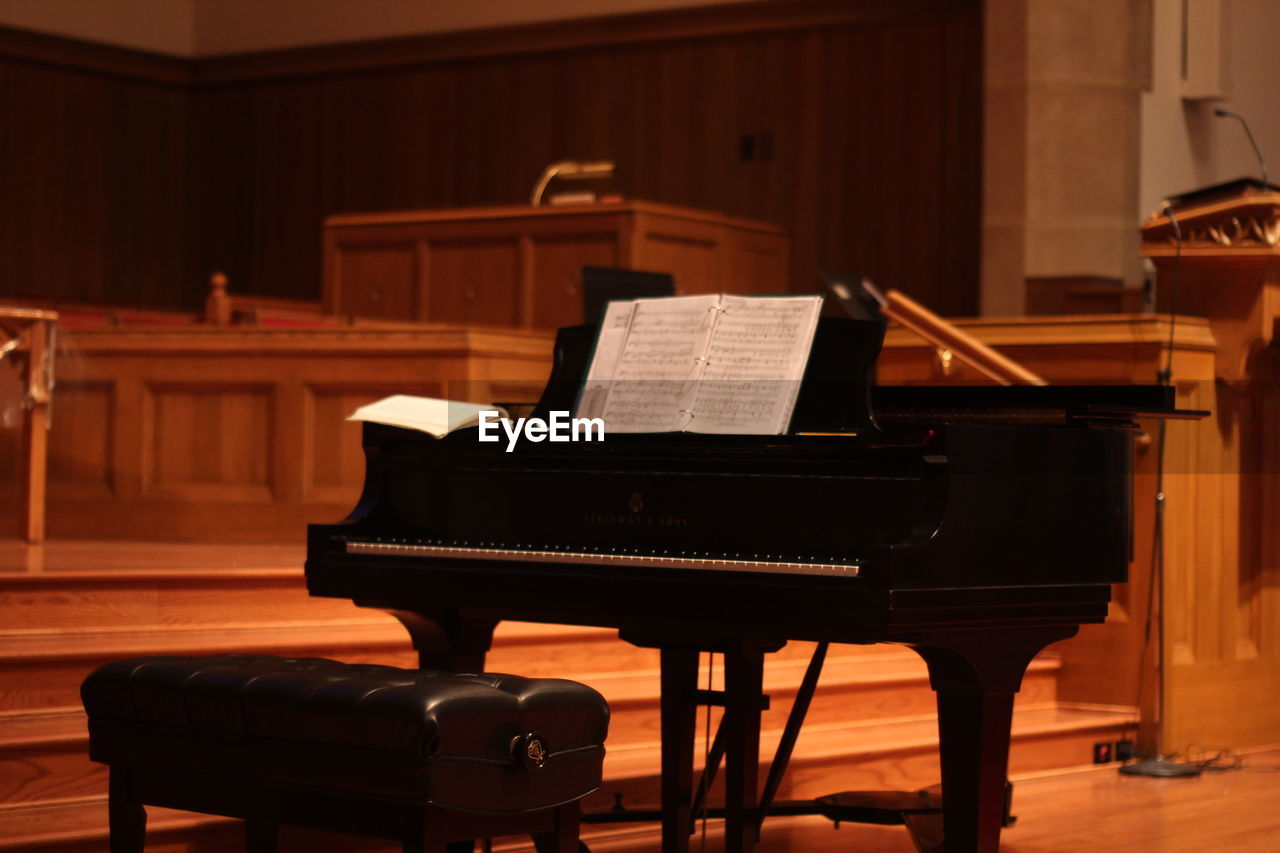 musical equipment, piano, musical instrument, music, arts culture and entertainment, indoors, sheet music, sheet, seat, grand piano, paper, classical music, wood - material, no people, keyboard instrument, skill, absence, focus on foreground, musical note, chair, keyboard, stage, piano key