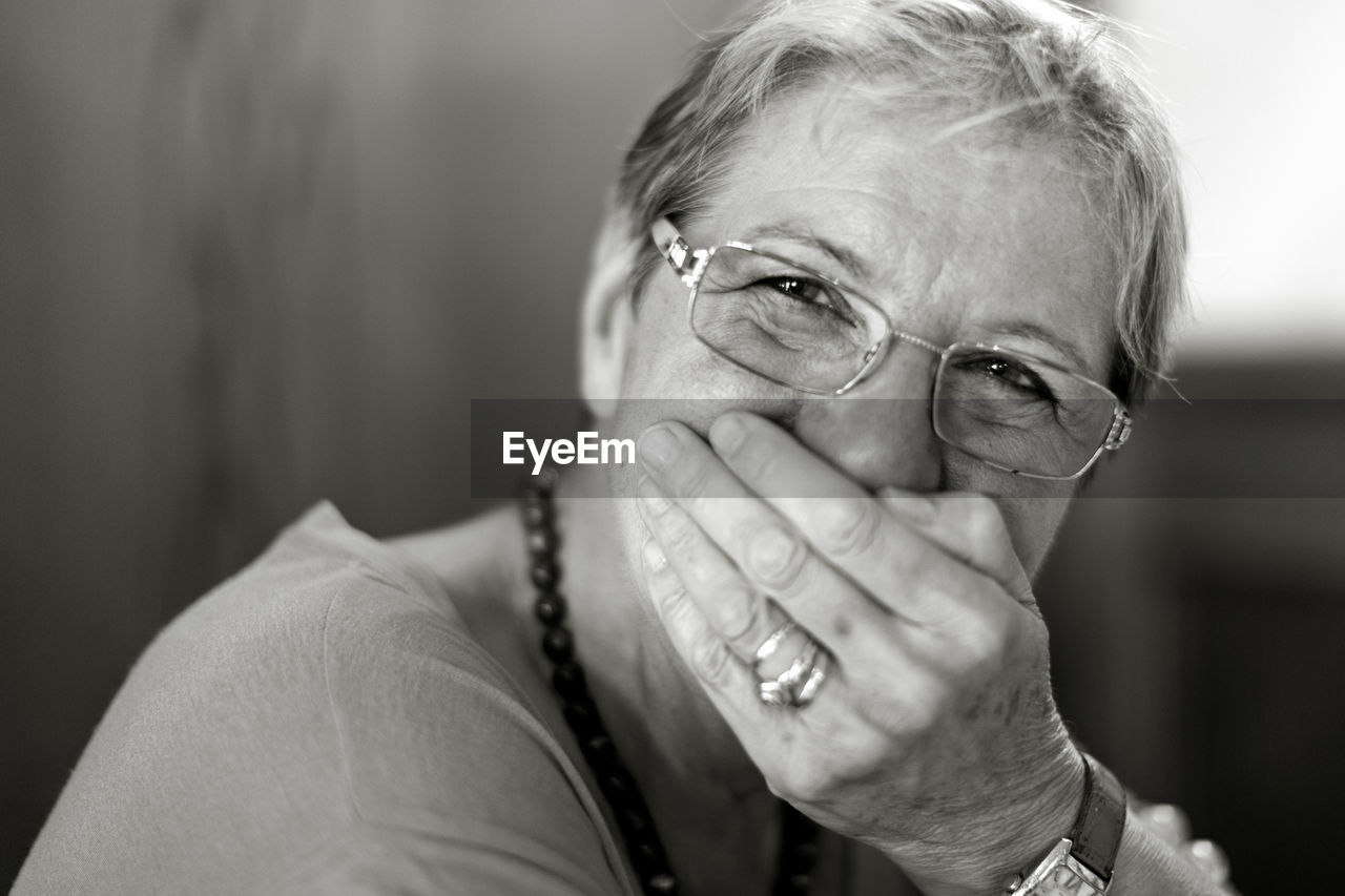 Portrait Of Woman Wearing Eyeglasses Covering Mouth