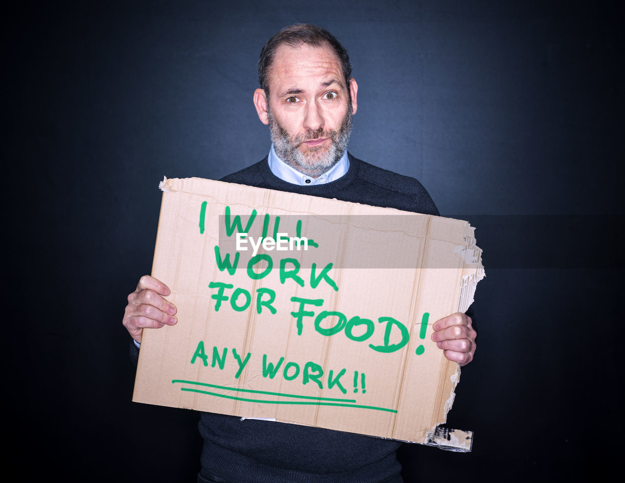 one person, studio shot, holding, looking at camera, text, portrait, black background, sign, indoors, western script, front view, cardboard, communication, mature adult, casual clothing, males, standing, men, adult, mature men, message, social issues, unemployment