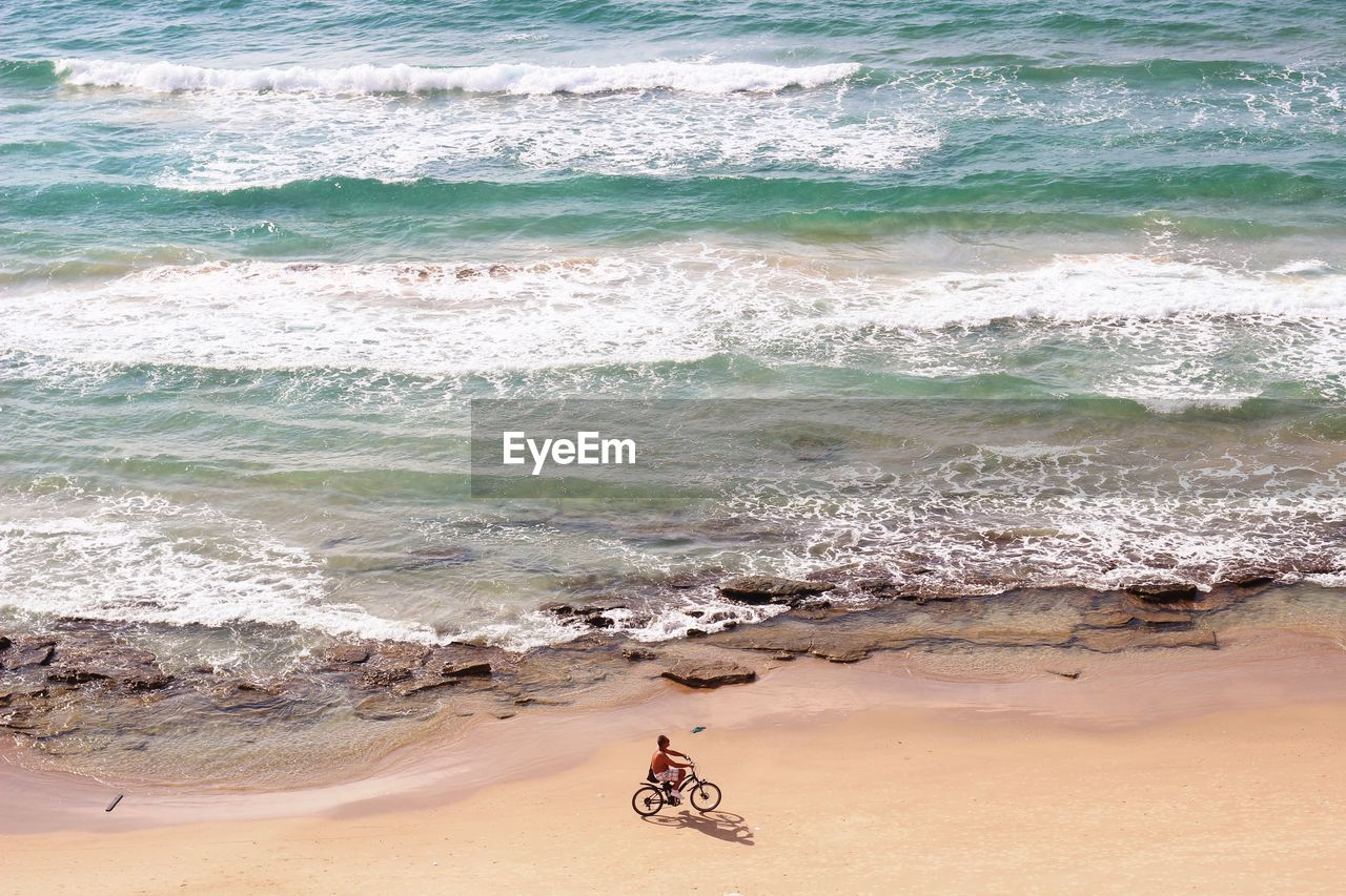 Aerial view of man bicycling on beach