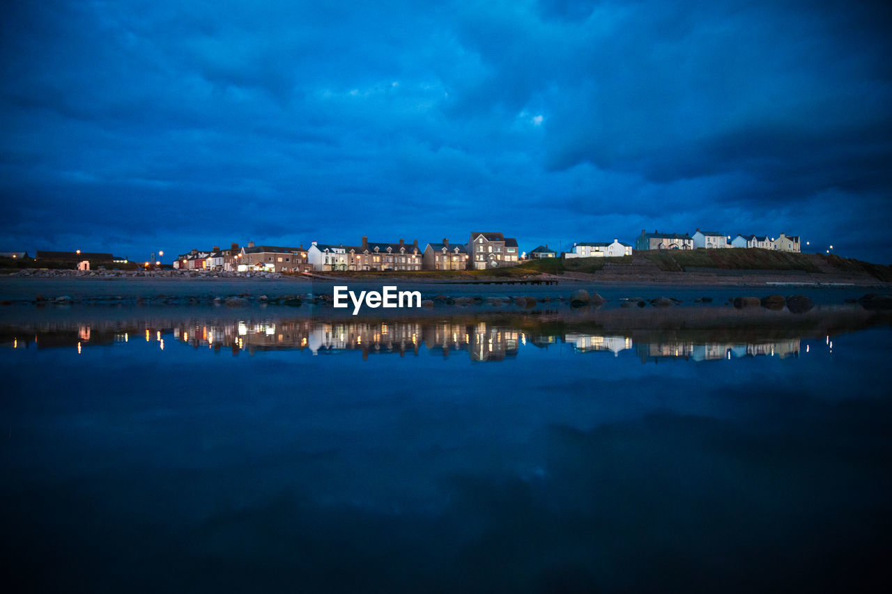 Scenic View Of Illuminated Town And Calm Lake Against Cloudy Night Sky
