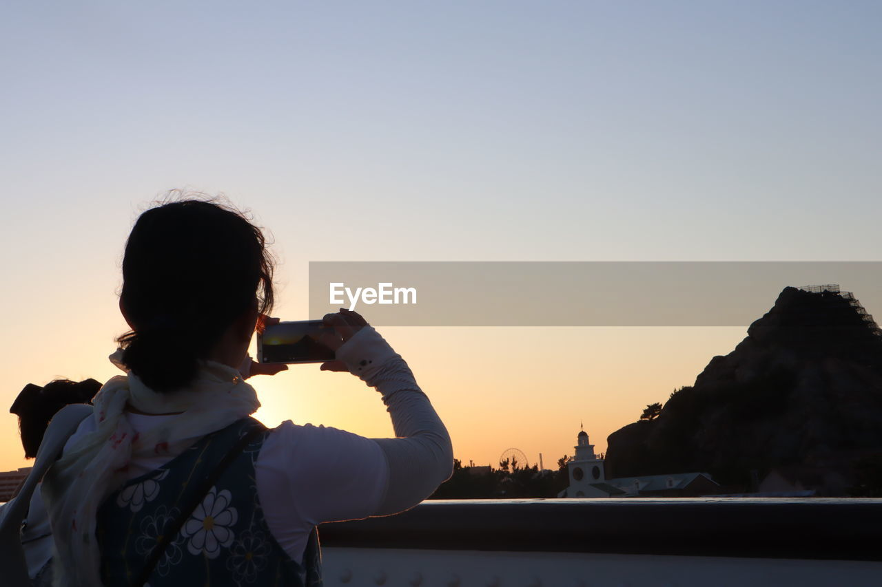 sky, sunset, real people, photography themes, lifestyles, photographing, one person, technology, rear view, holding, nature, leisure activity, clear sky, wireless technology, copy space, waist up, mobile phone, women, activity, outdoors