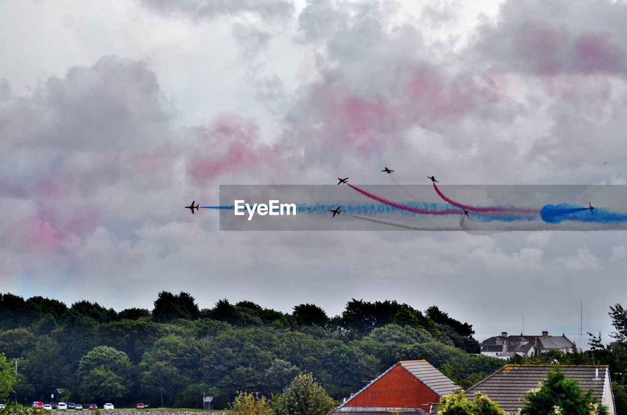 Airplanes with vapor trail in sky during airshow