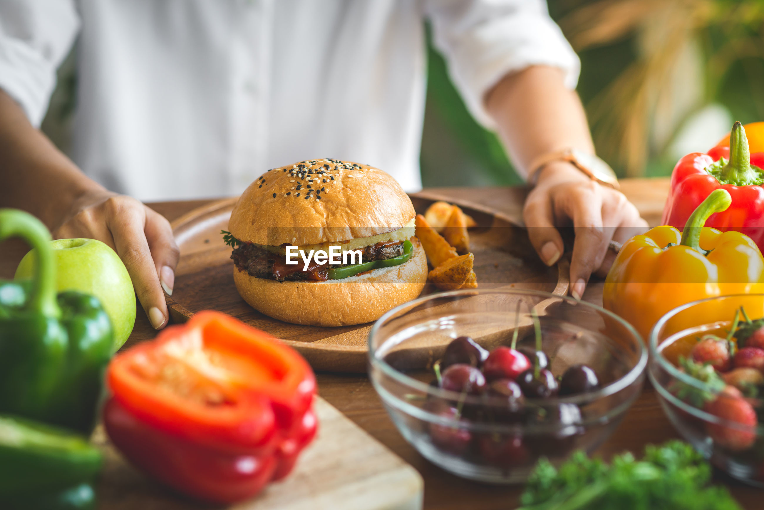 Close-up of woman with burger on table