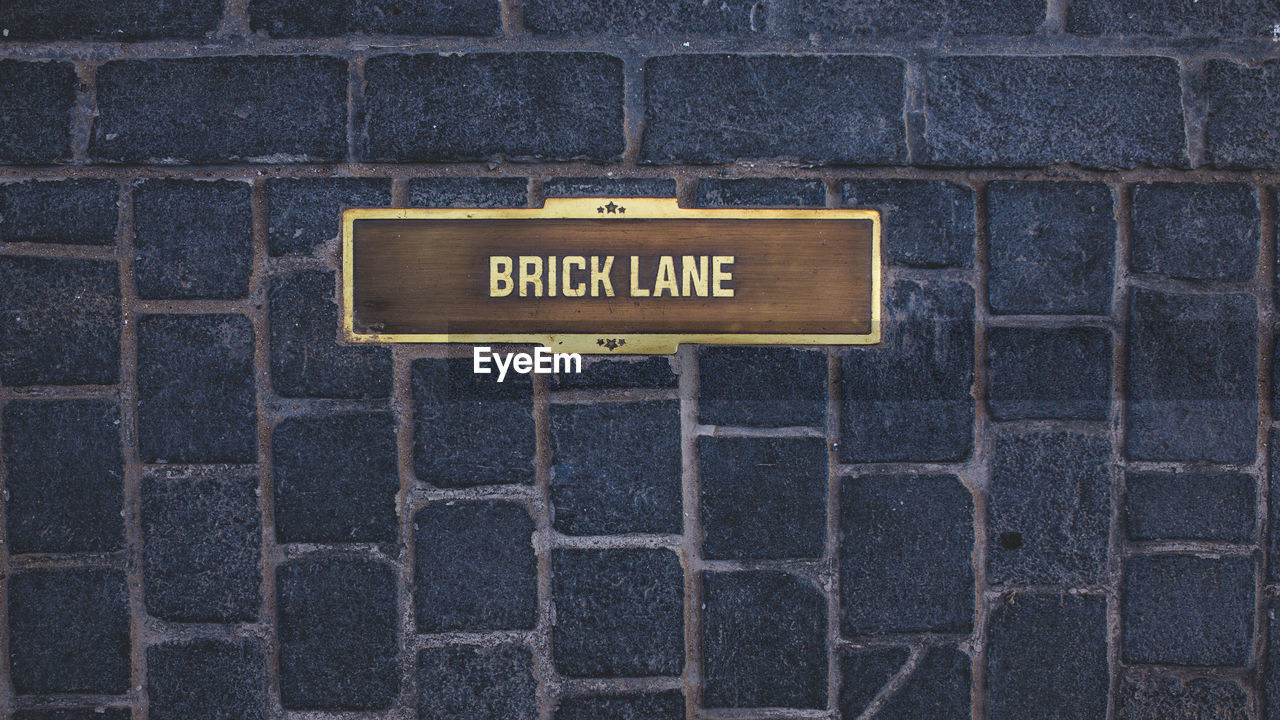western script, text, sign, communication, wall - building feature, wall, capital letter, no people, brick, information, brick wall, day, architecture, pattern, built structure, information sign, script, non-western script, outdoors, close-up, message