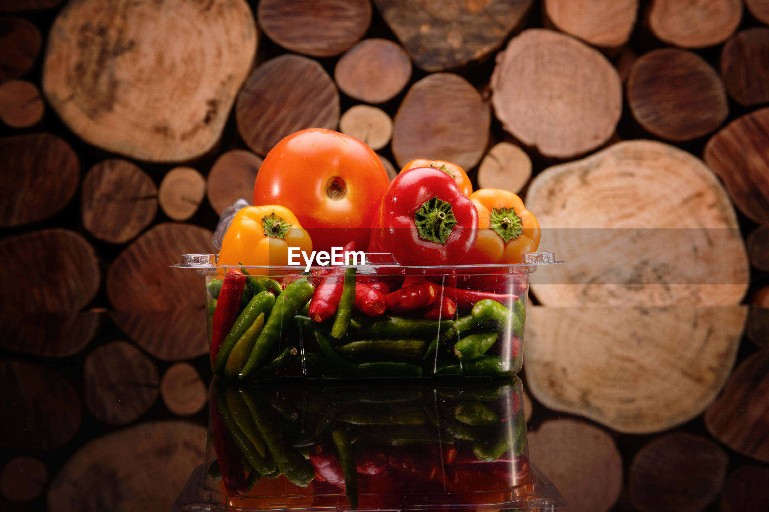 Close-up of vegetables in container against stacked logs