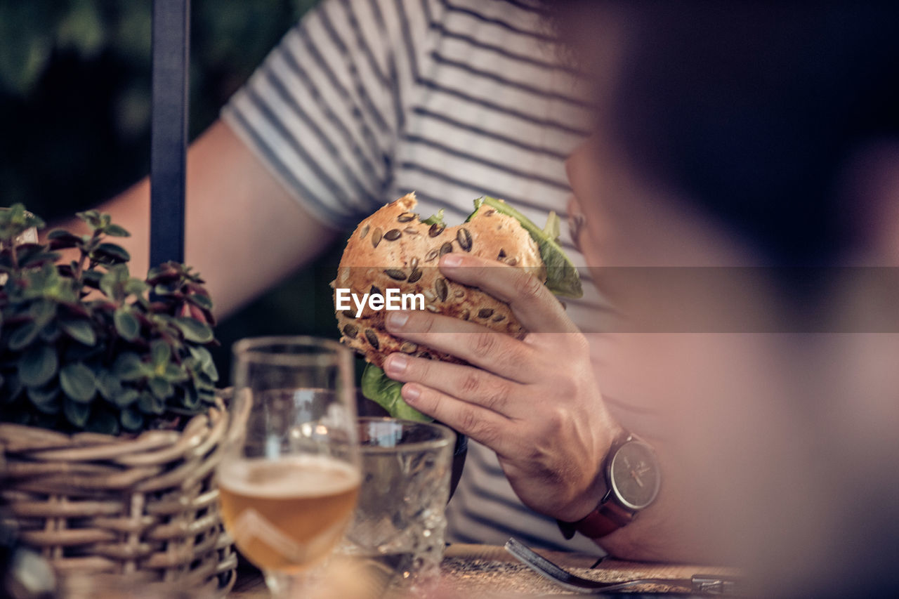 Midsection of man having burger in restaurant