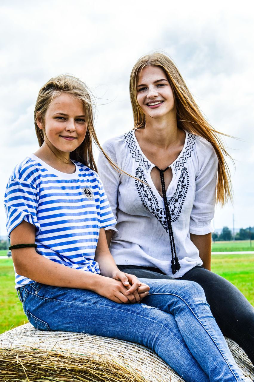 Portrait of smiling siblings sitting on hay bale against sky