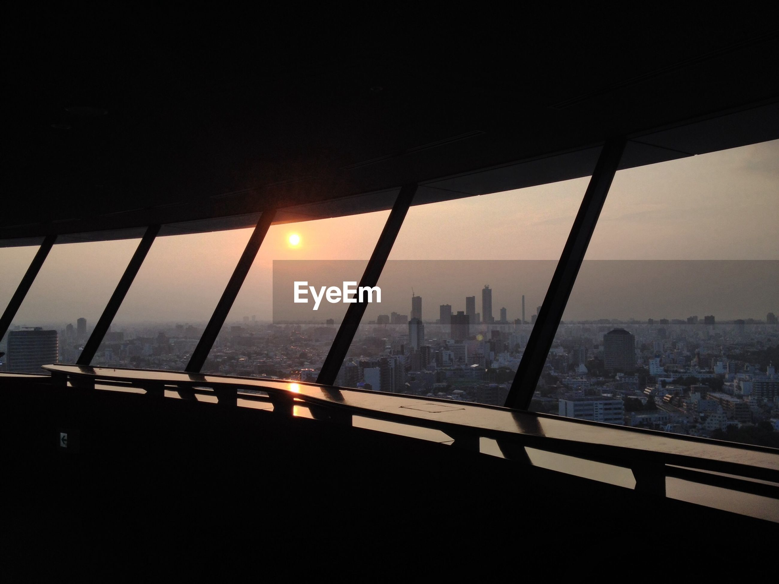 architecture, built structure, cityscape, city, building exterior, sky, glass - material, skyscraper, indoors, river, window, transparent, modern, water, sunset, bridge - man made structure, office building, connection, railing, silhouette