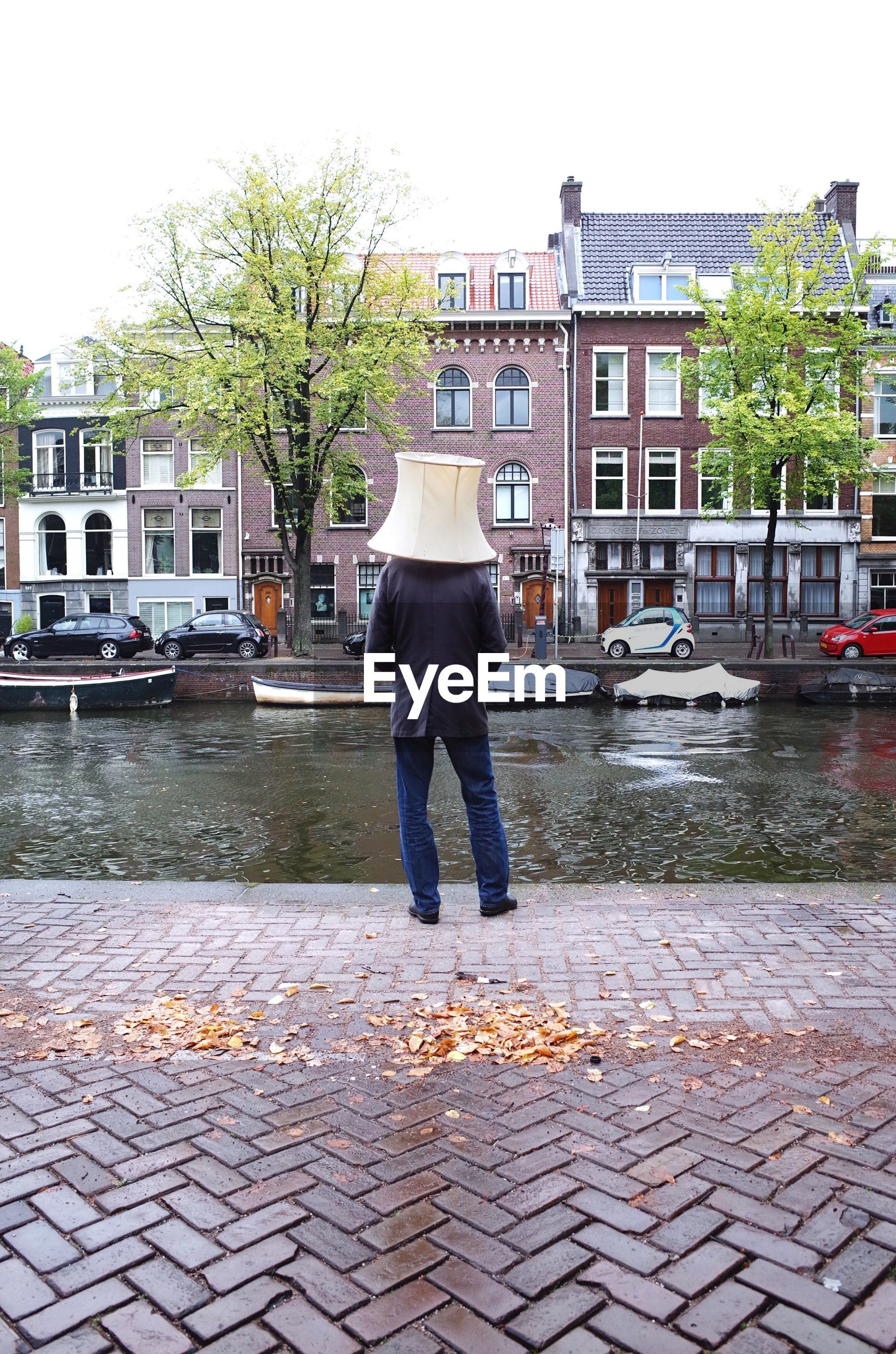 Man wearing lamp shade while standing by canal