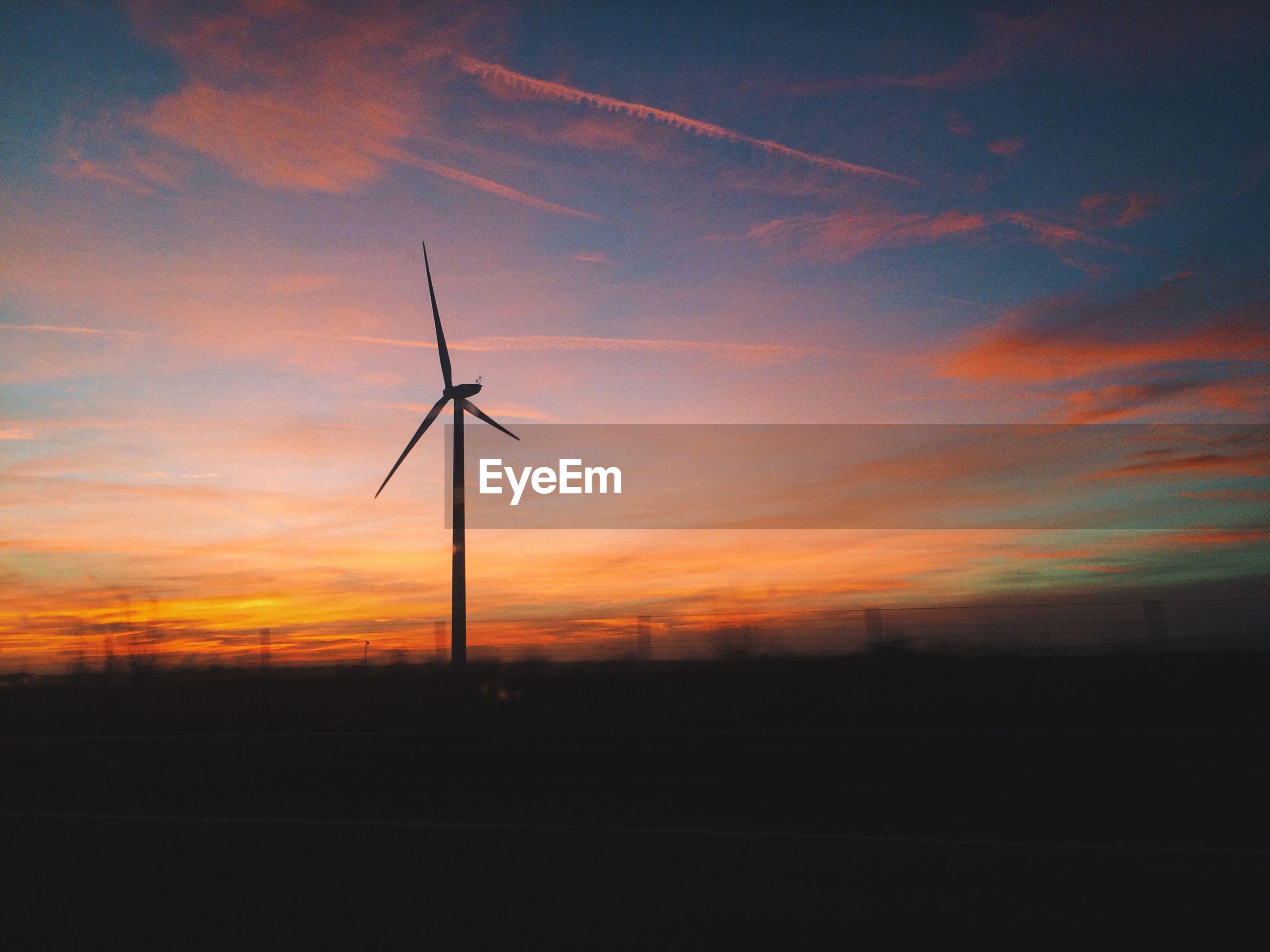 Wind turbine on silhouette landscape against dusk