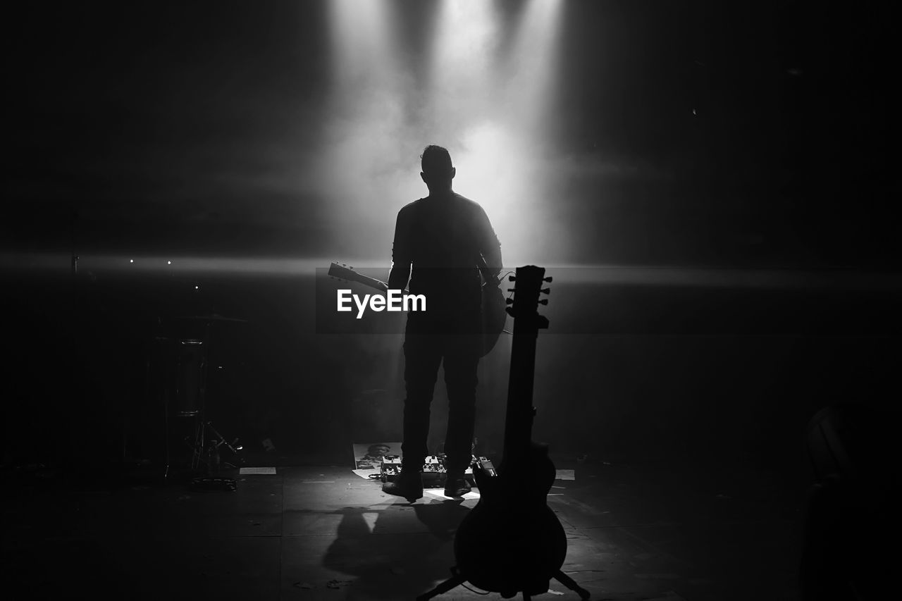 Silhouette Man Standing With Guitar At Night