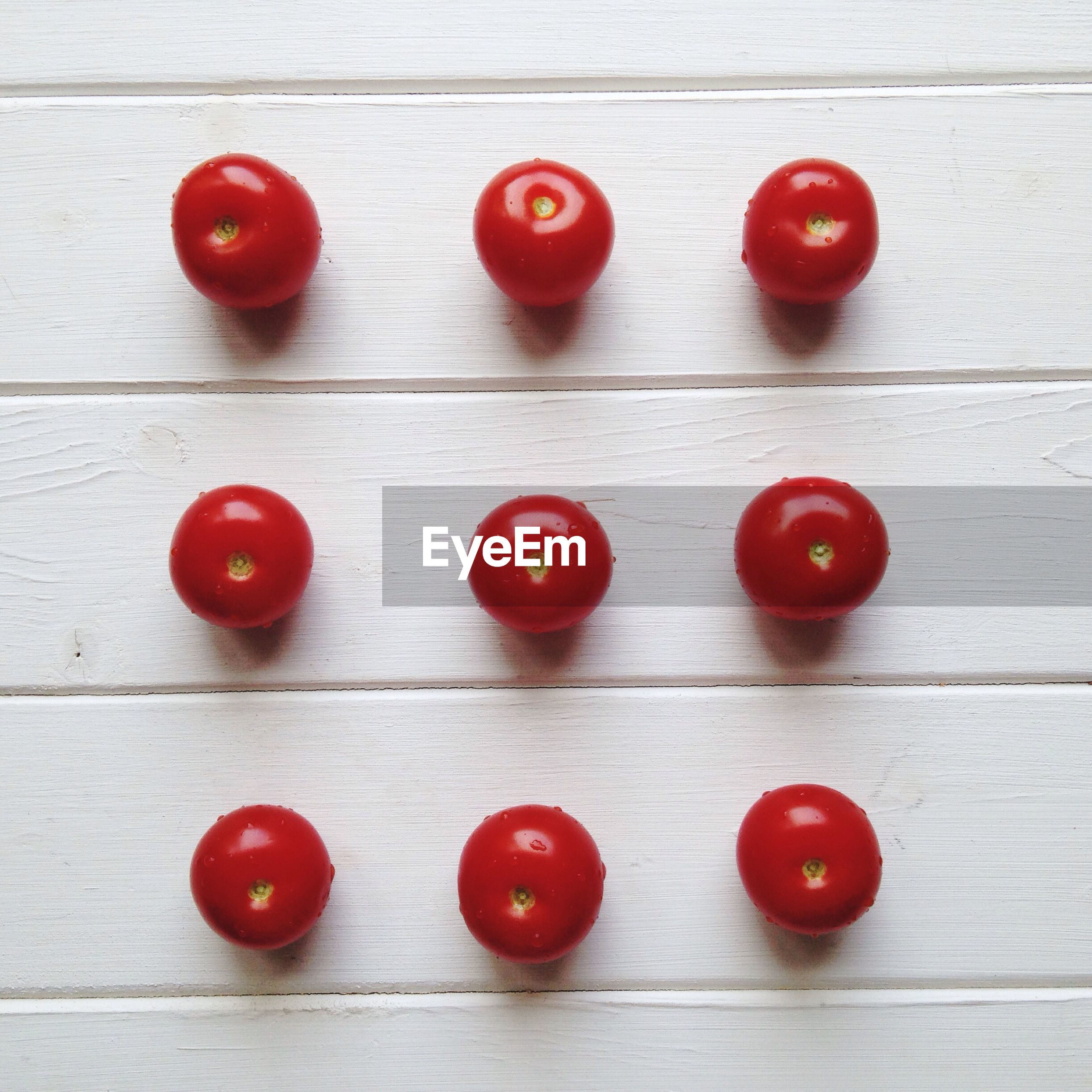 Directly above shot of wet tomatoes on white wooden table