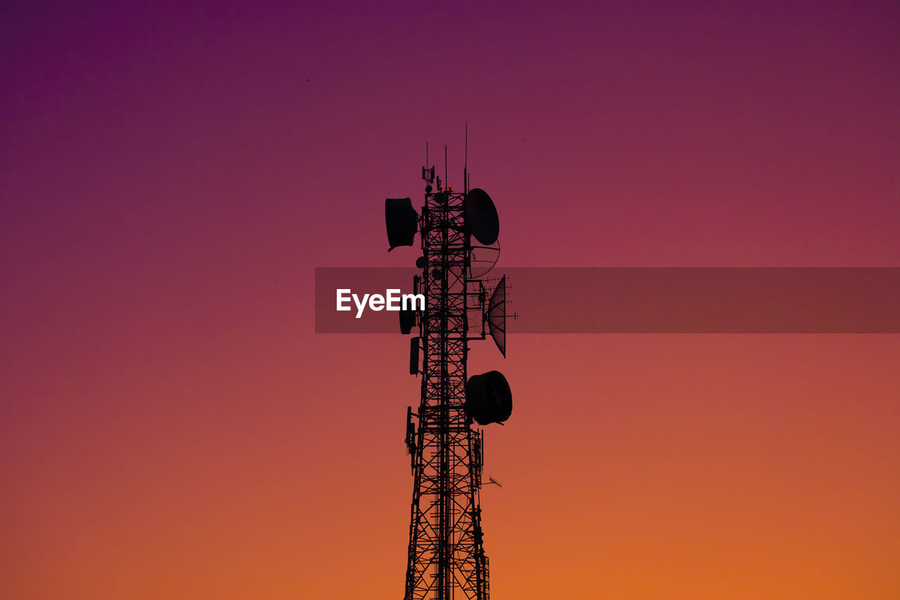 Low angle view of communications tower against clear sky during sunset