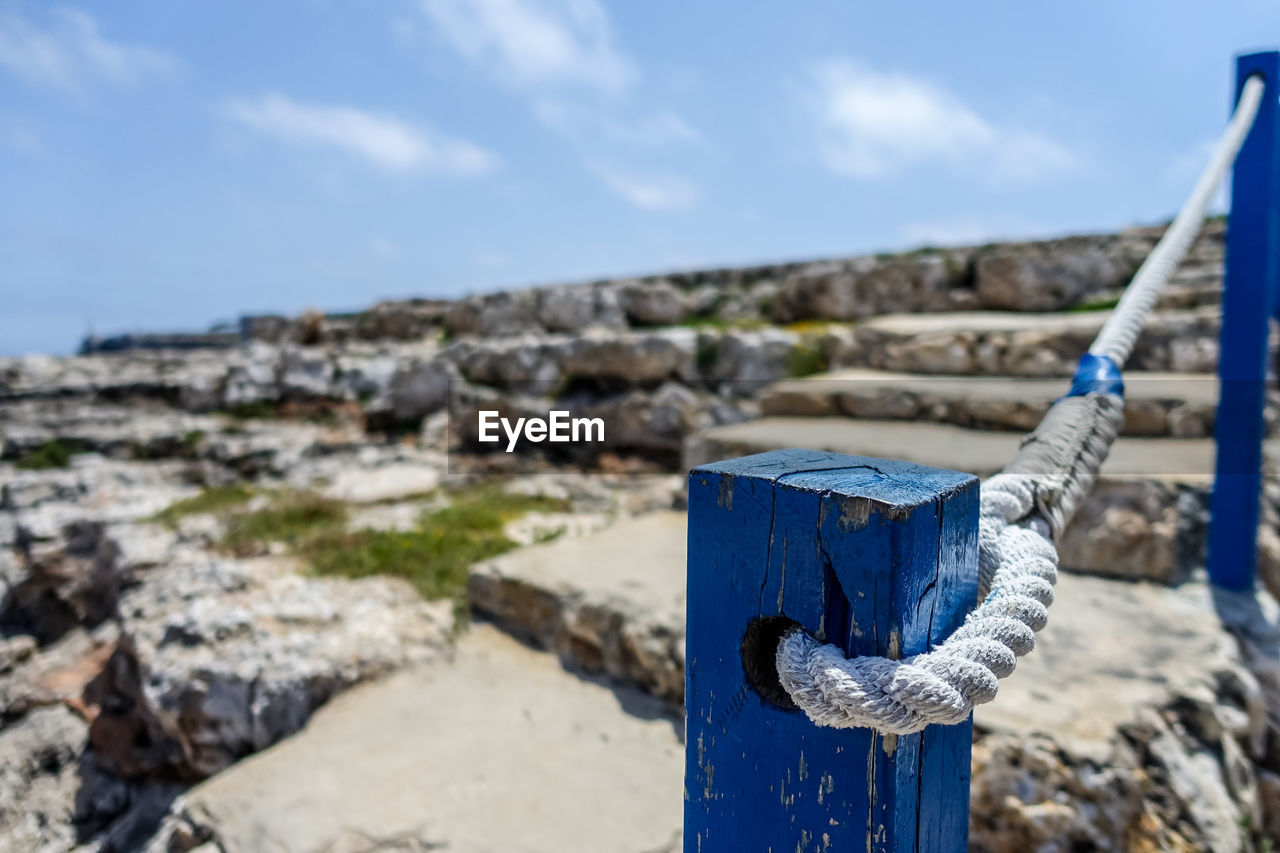 focus on foreground, blue, day, nature, no people, sky, close-up, solid, outdoors, metal, land, wood - material, architecture, sunlight, rock, built structure, rock - object, beach, rope, old, concrete