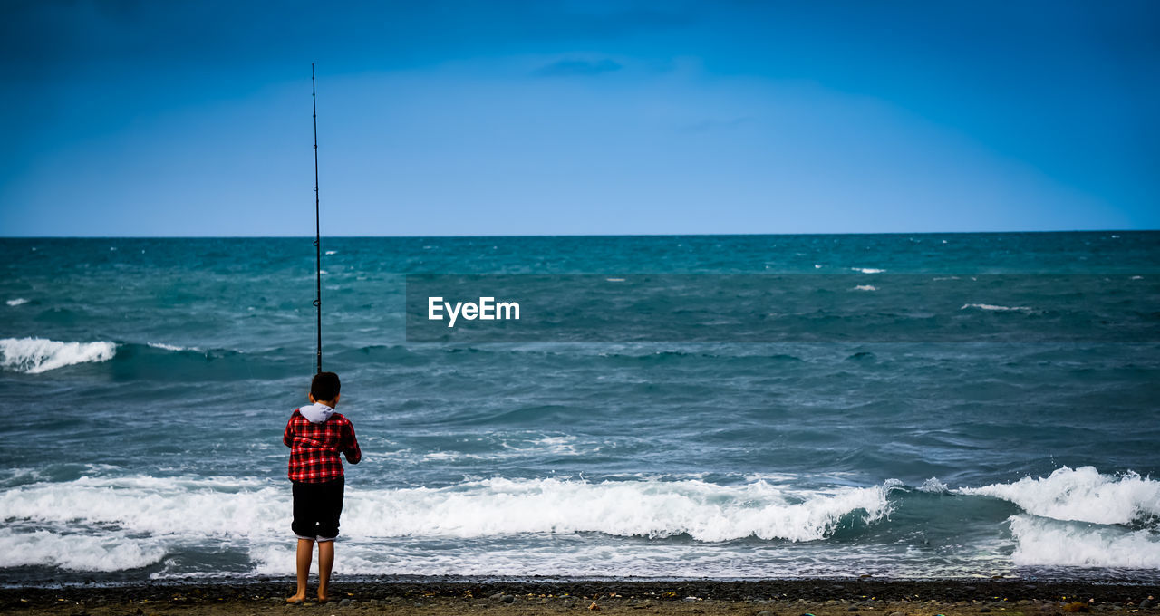 Rear view of boy fishing at beach against blue sky