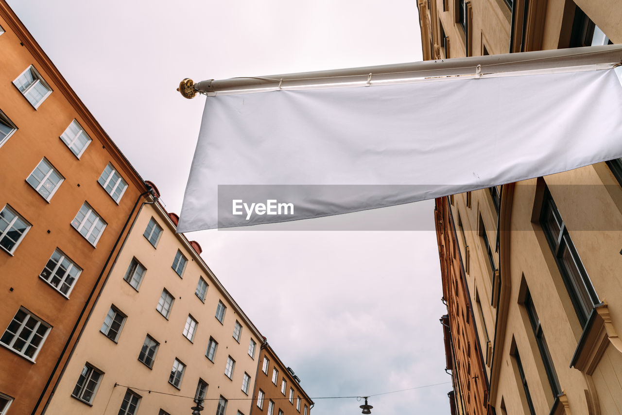 Horizontal white empty banner on clothes shop front against old buildings in city