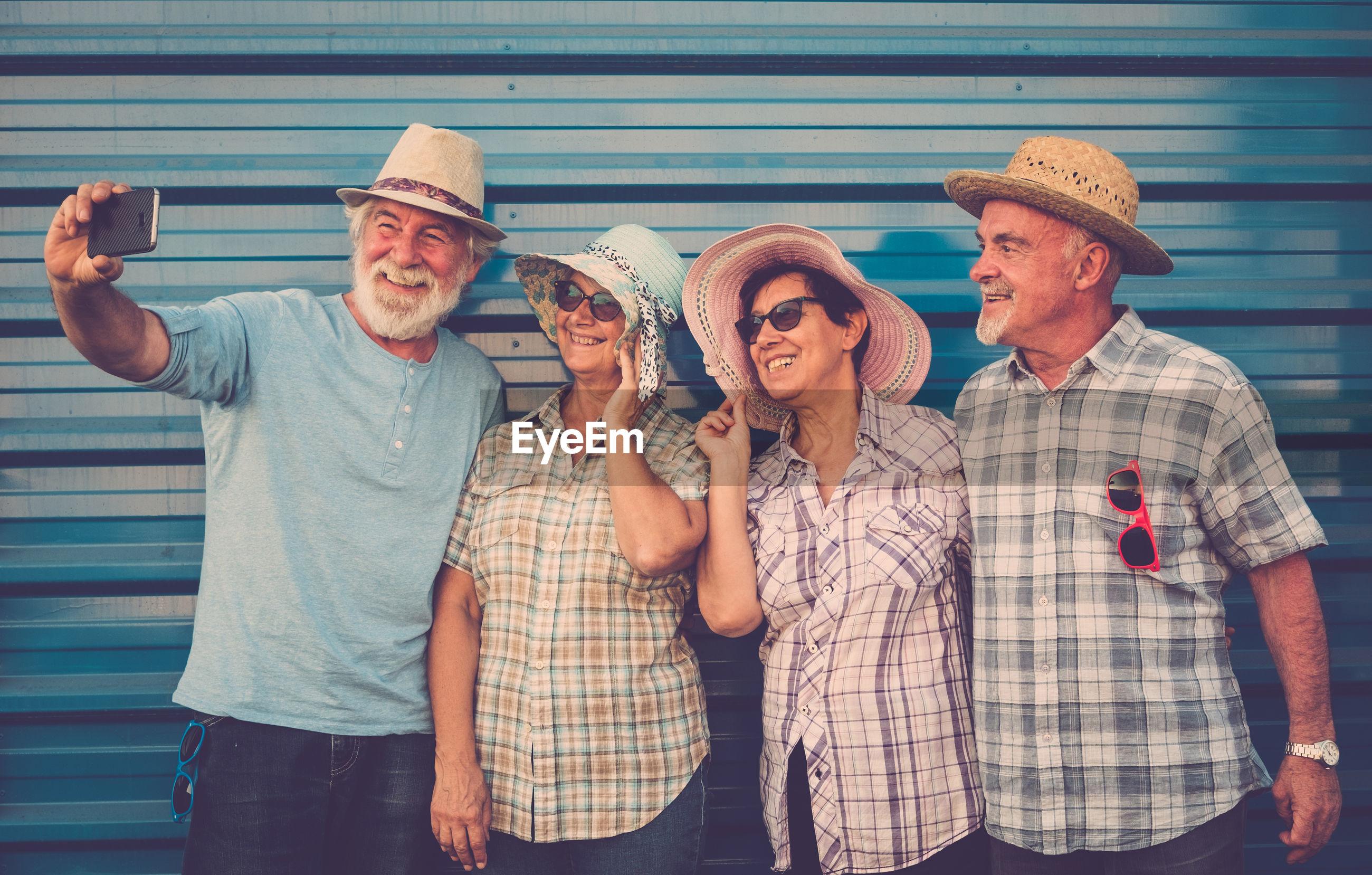 Senior friends taking selfie against wall