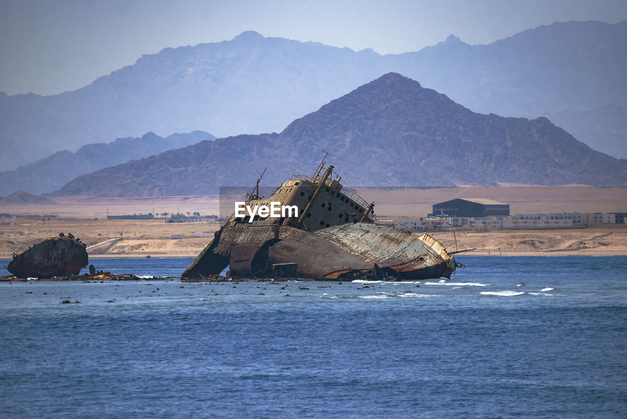 Shipwreck in sea against mountains
