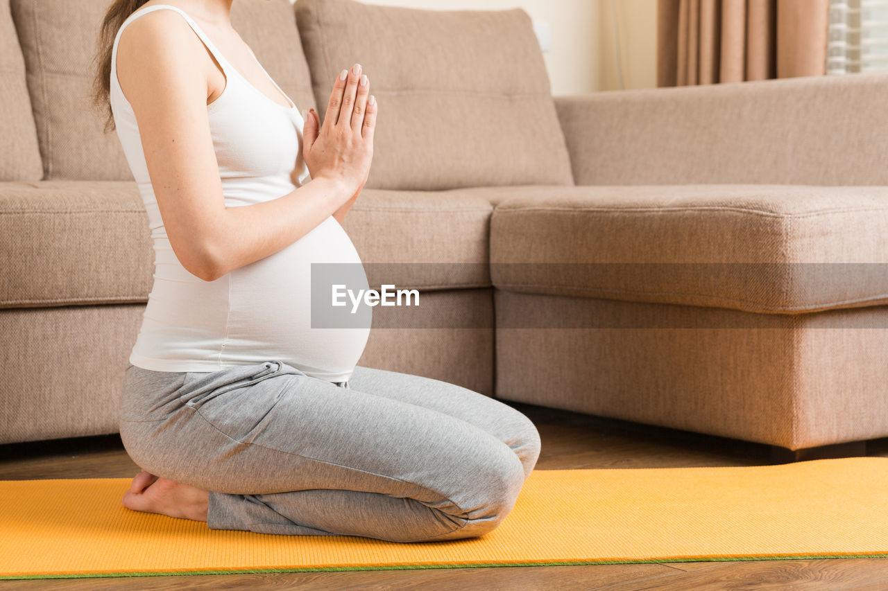 LOW SECTION OF WOMAN SITTING AT SOFA