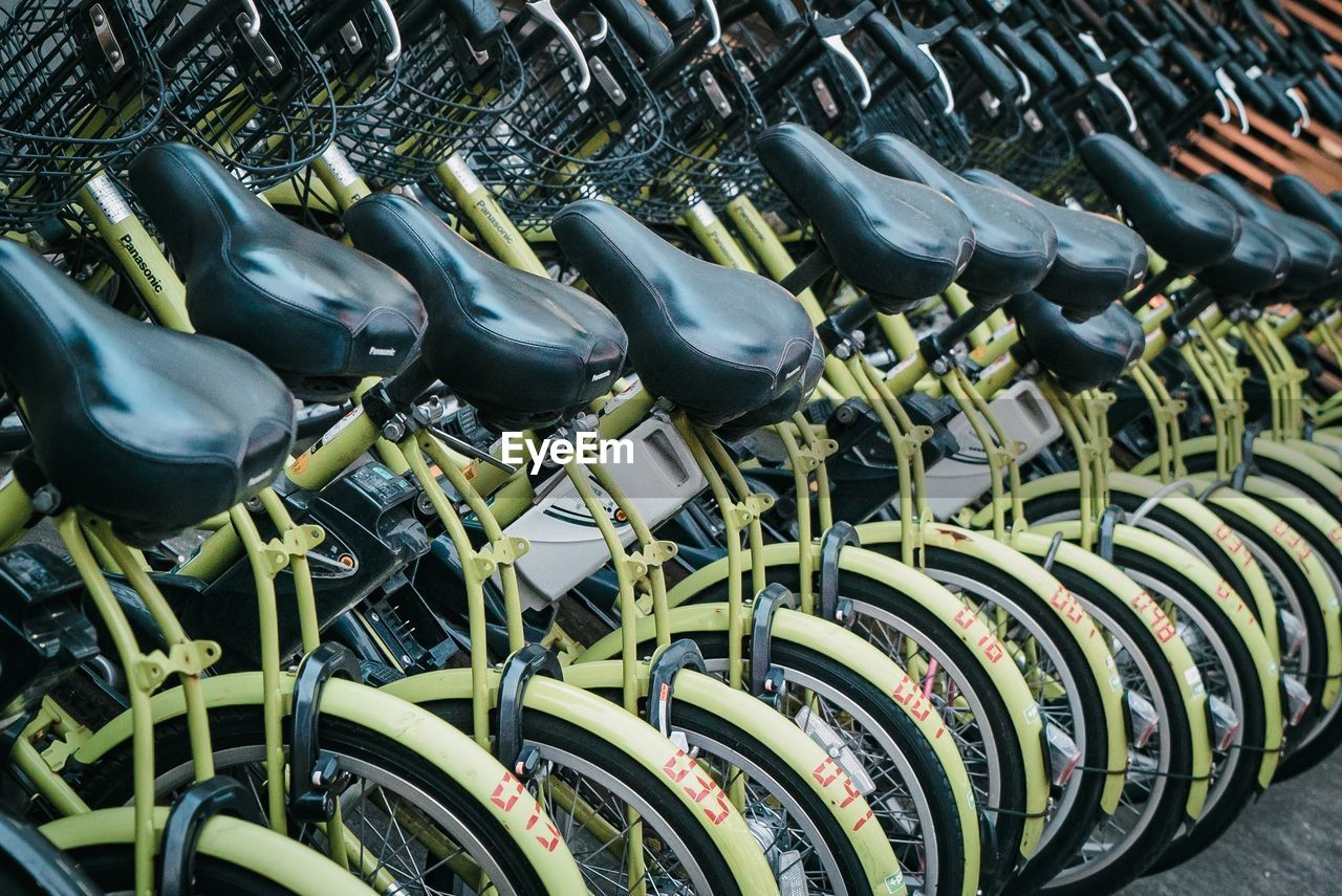 large group of objects, abundance, no people, in a row, bicycle, retail, metal, rack, arrangement, order, side by side, repetition, day, transportation, indoors, still life, for sale, close-up, business, wheel