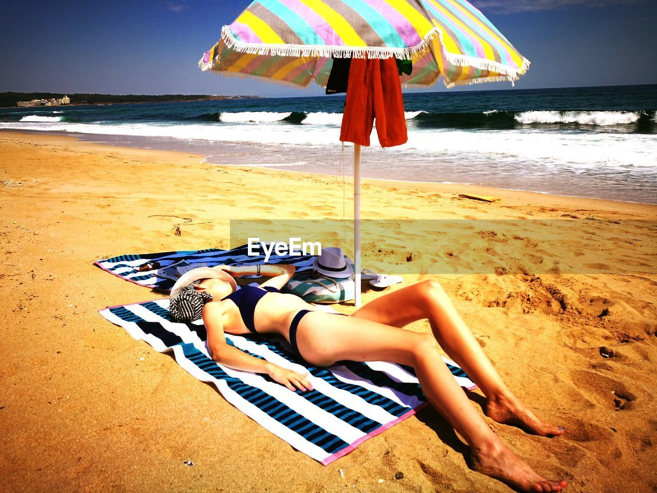 beach, sand, sea, shore, horizon over water, vacations, water, summer, real people, day, leisure activity, bikini, one person, nature, beauty in nature, lying down, outdoors, relaxation, full length, women, low section, sky, young adult