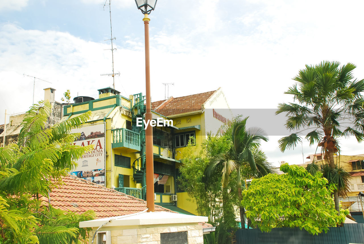 tree, built structure, sky, building exterior, architecture, plant, palm tree, tropical climate, nature, building, growth, green color, cloud - sky, day, no people, residential district, outdoors, house, roof, low angle view, coconut palm tree