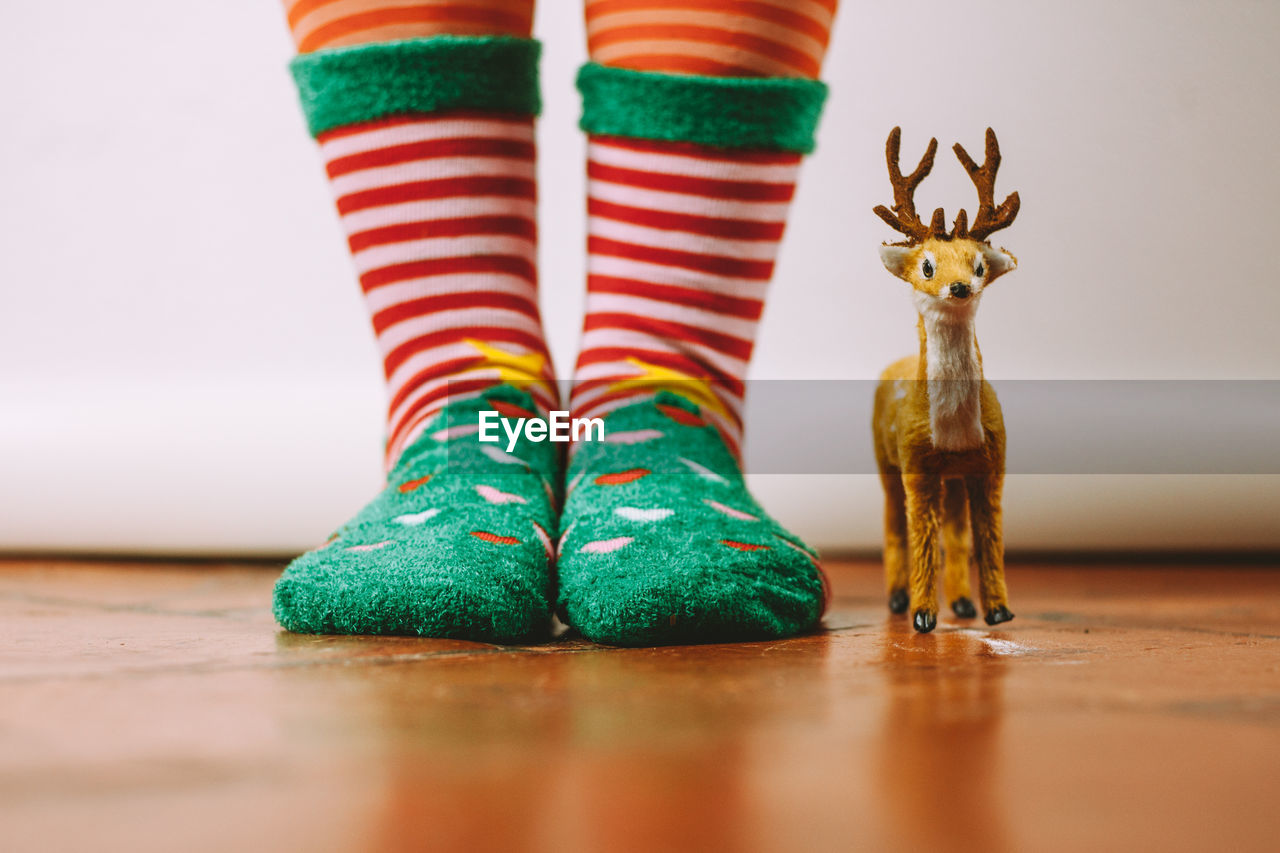 Low section of person wearing sock by deer toy on floor
