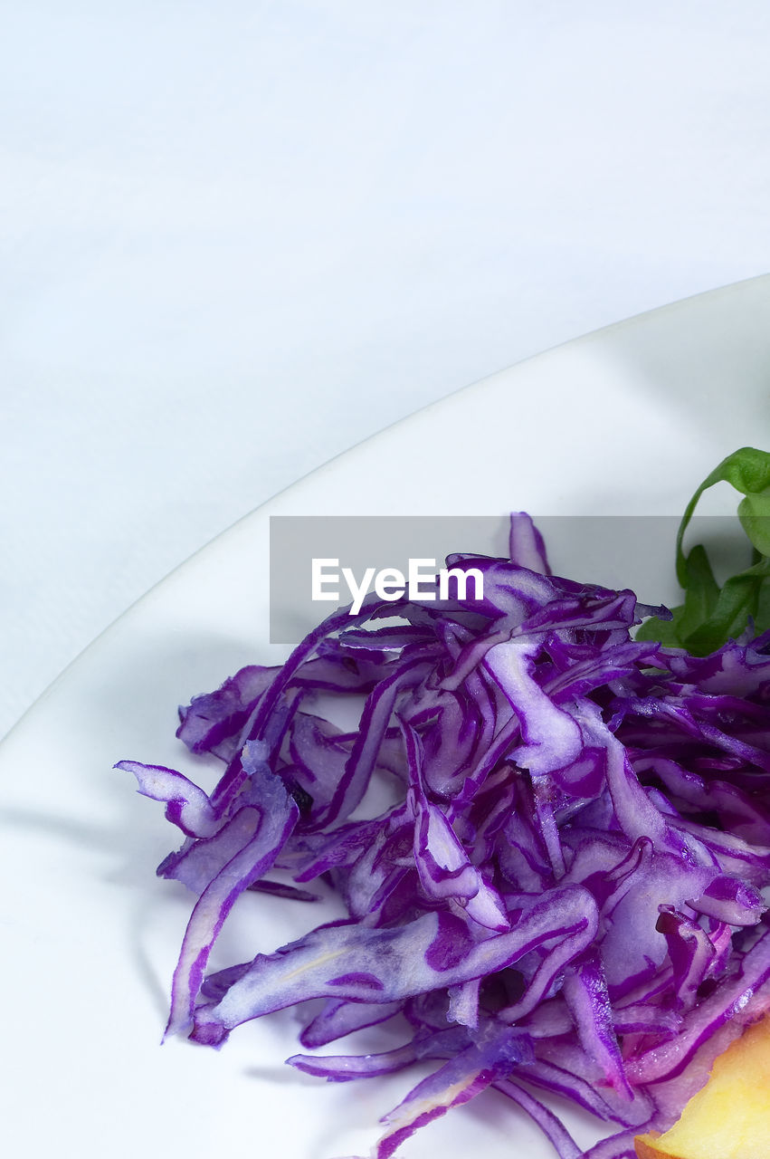 Close-Up Of Red Cabbage In Plate Against White Background