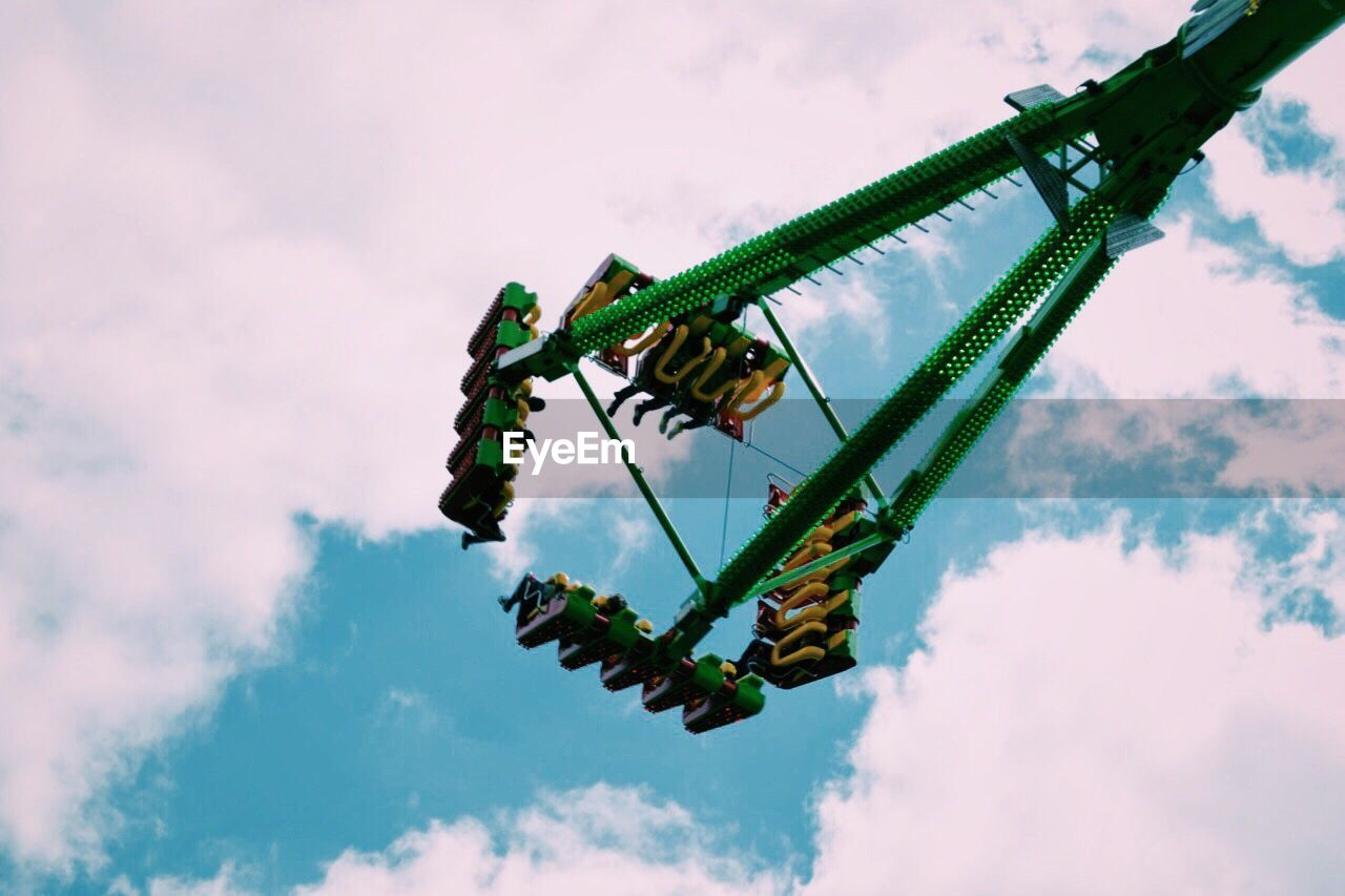 Low Angle View Of People In Amusement Park Ride Against Cloudy Sky
