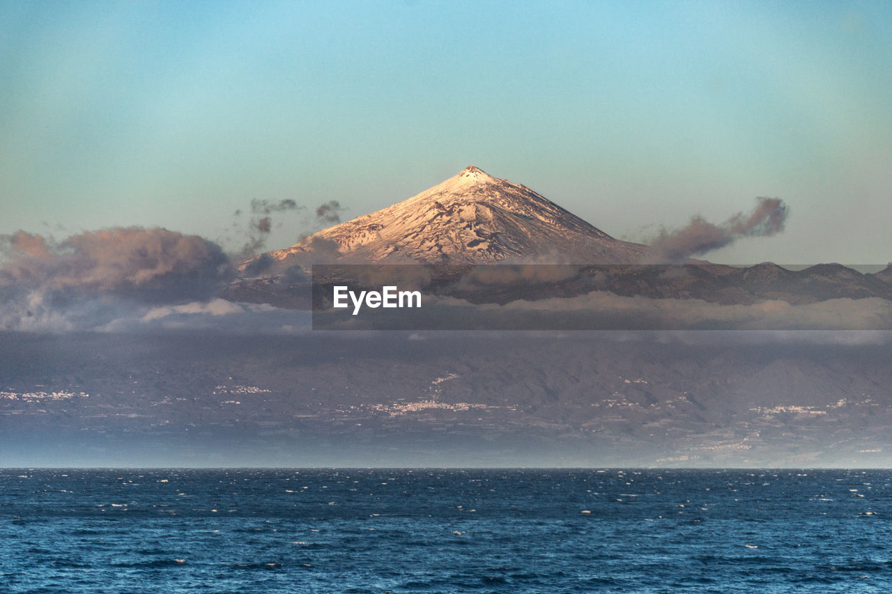 SCENIC VIEW OF SEA AGAINST MOUNTAIN