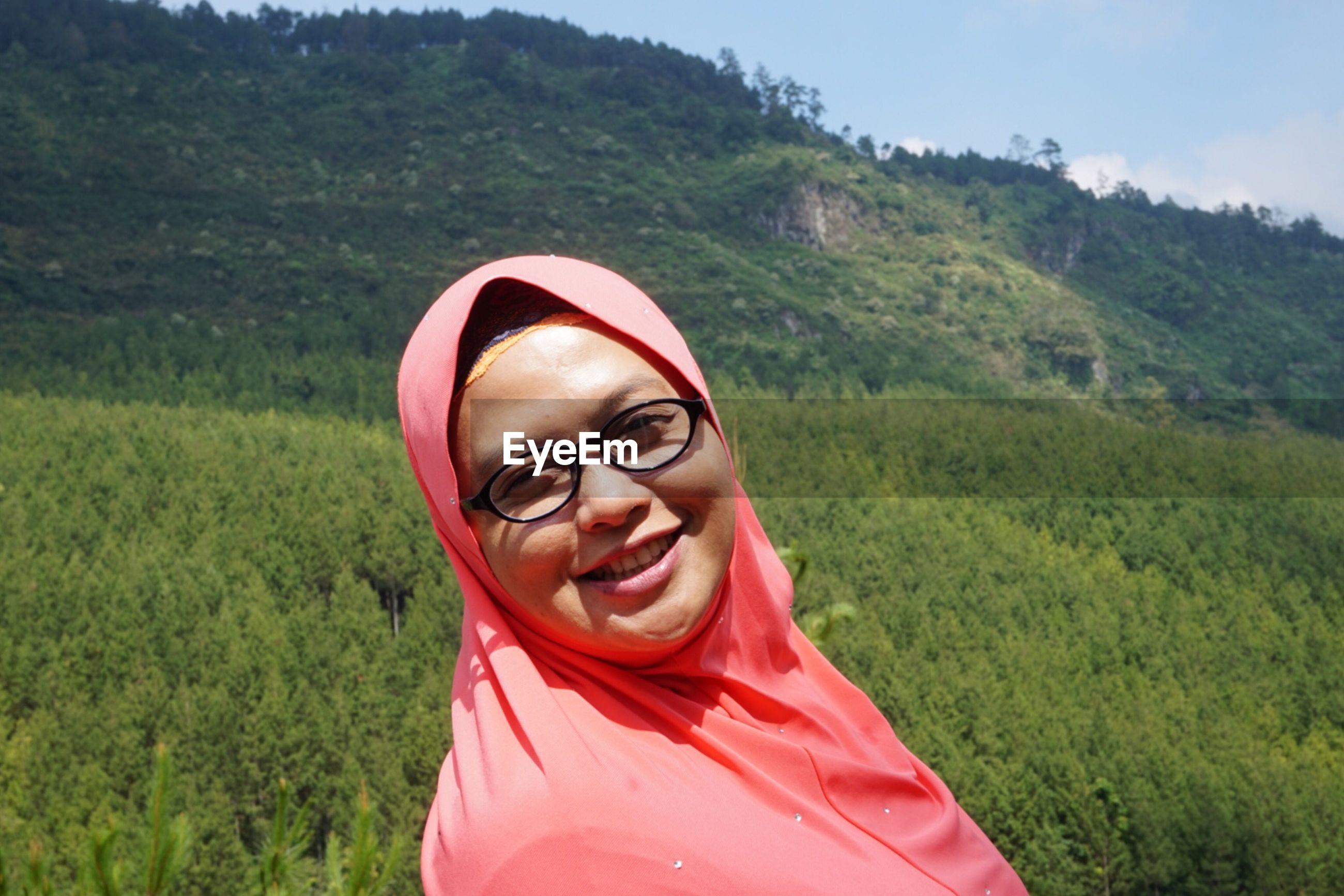 Portrait of cheerful young woman wearing hijab and eyeglasses against mountain during sunny day